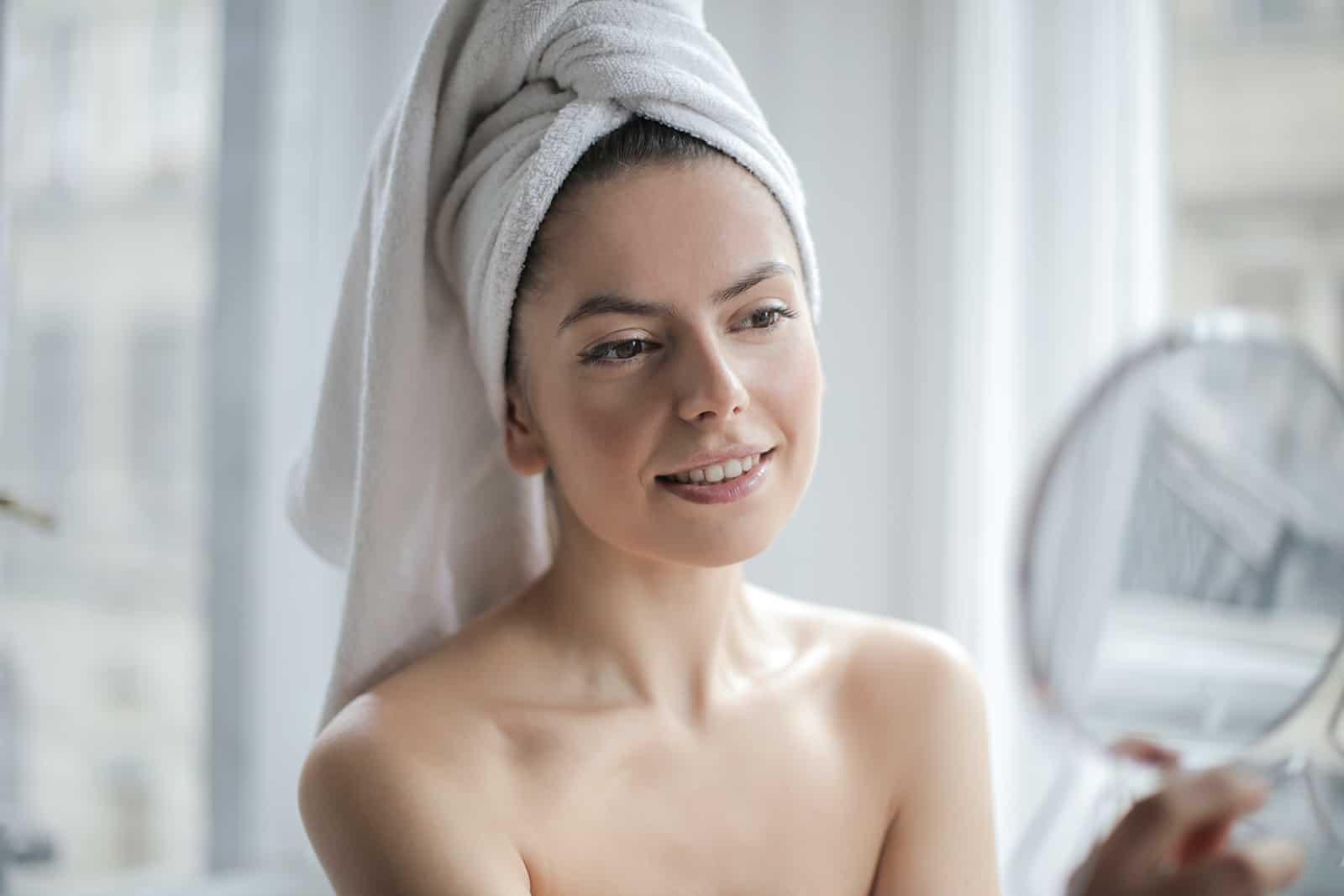 eine Frau mit einem Handtuch auf dem Kopf, die einen Spiegel hält und sich selbst ansieht