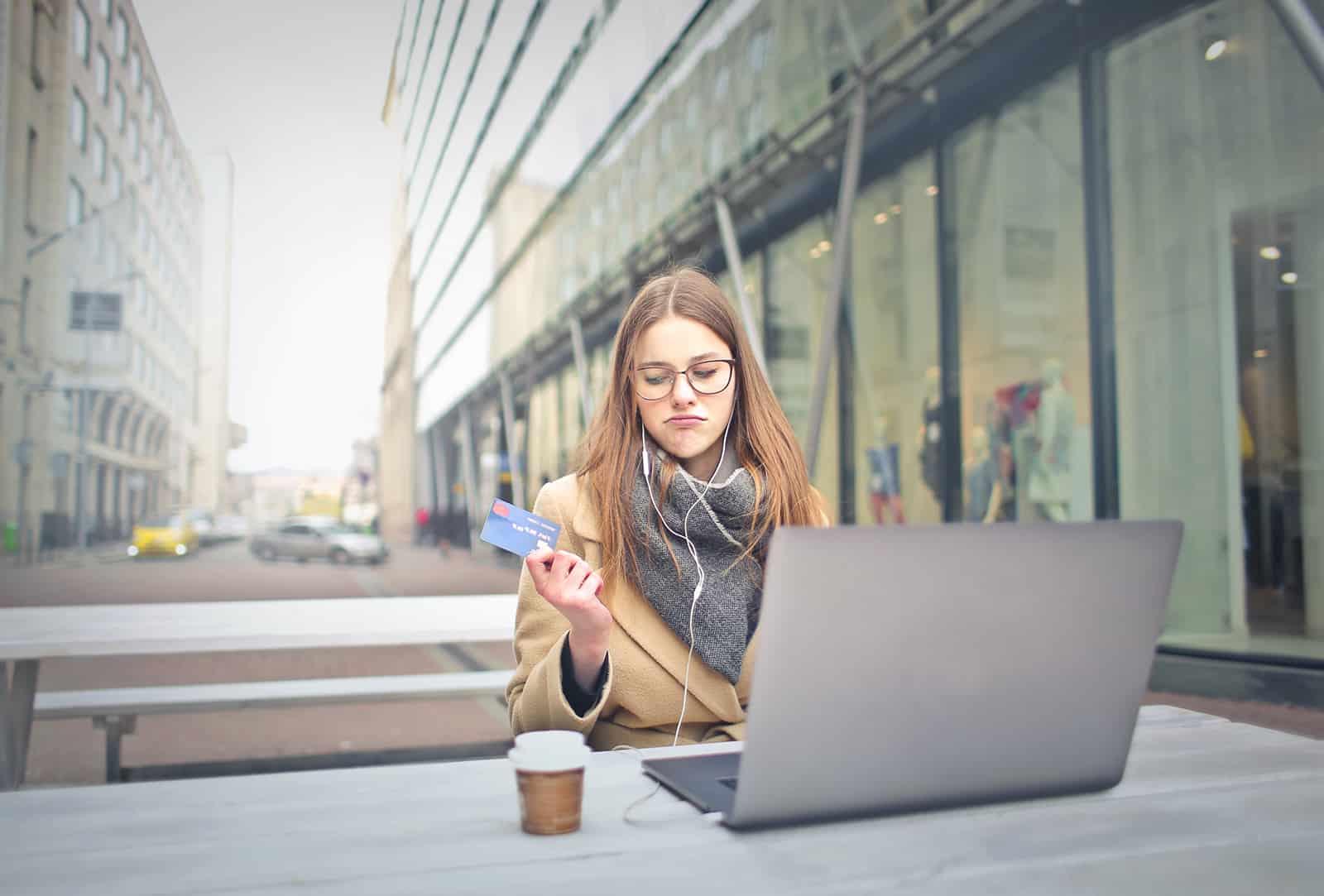 eine Frau, die eine Kreditkarte hält und darüber nachdenkt, Geld auszugeben oder zu sparen
