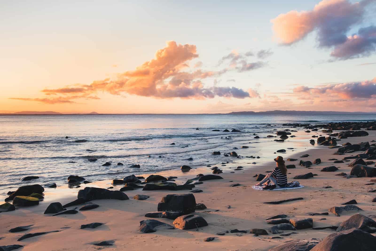 eine Frau, die am Strand sitzt und Sonnenuntergang beobachtet
