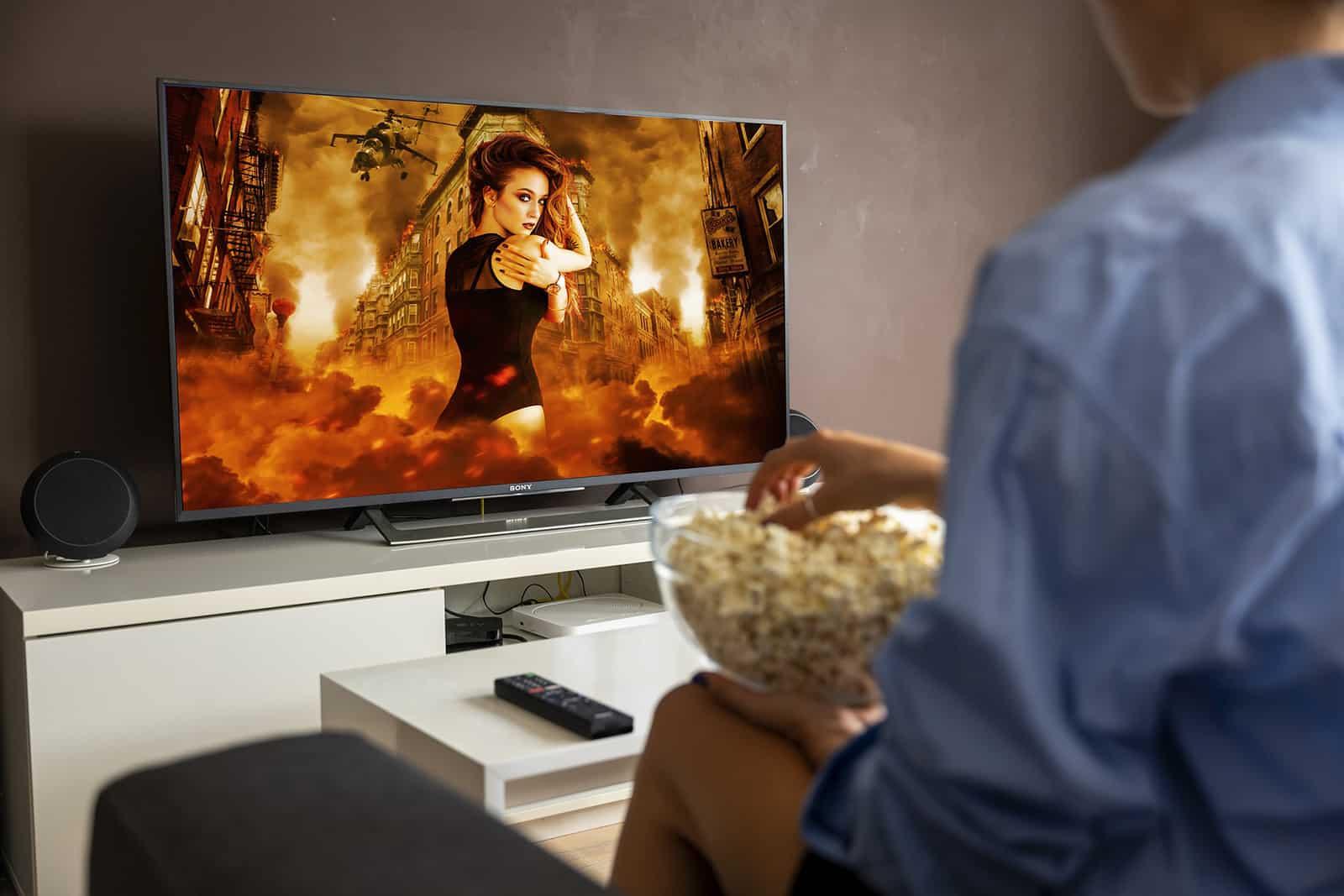 eine Frau, die vor dem Fernseher sitzt und einen Film sieht