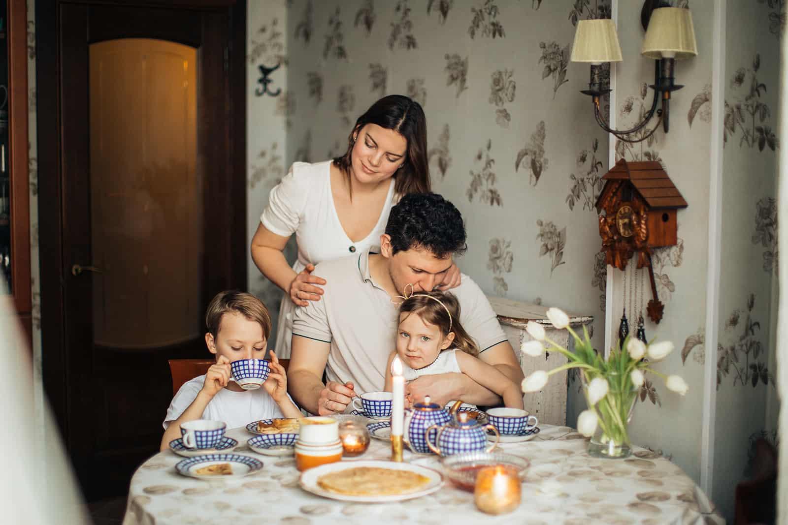 eine Frau umarmt ihren Mann, der mit Kindern am Tisch während einer Mahlzeit sitzt