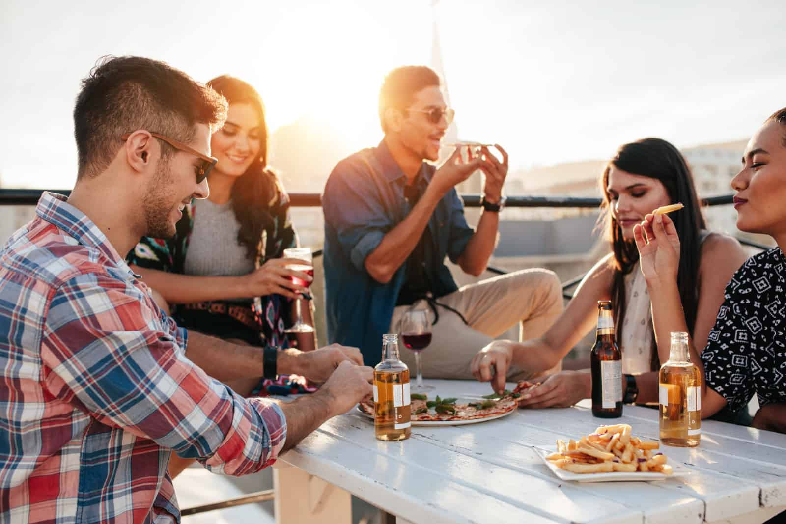 eine Gruppe junger Leute, die zusammen sitzen und Pizza essen