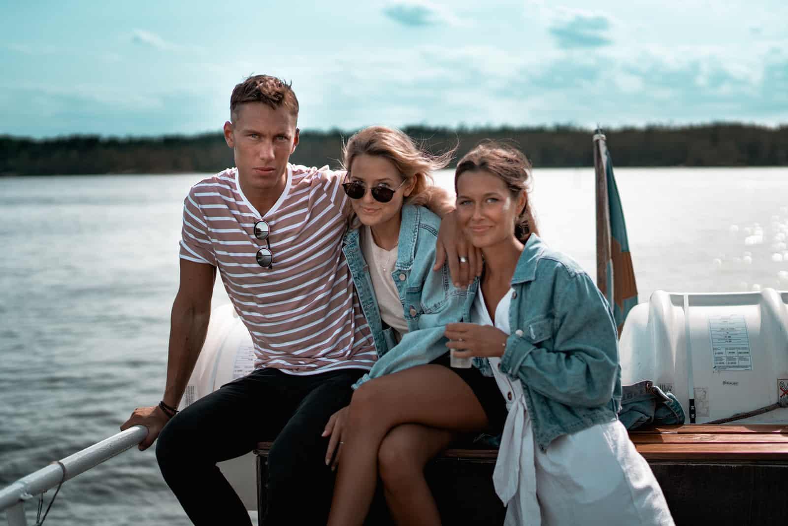 eine Gruppe von Freunden, die auf einem Boot sitzen, während sie für ein Foto posieren