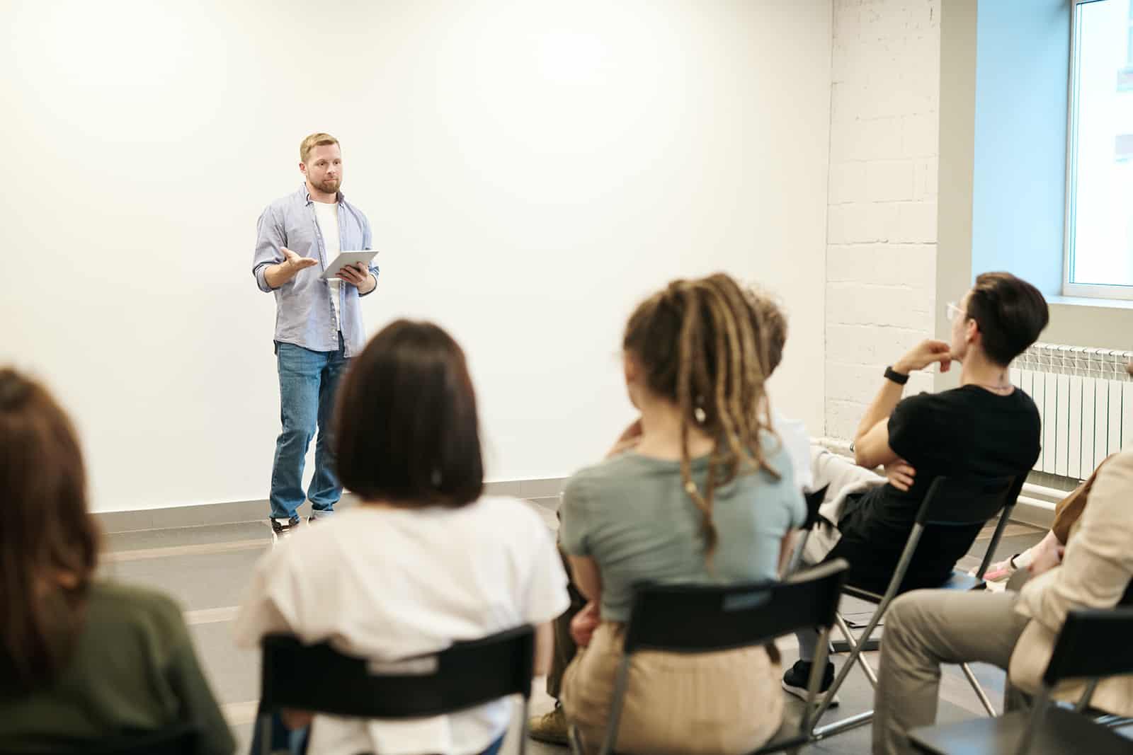 Eine Gruppe von Menschen hört sich einen Vortrag an, während ein Mann vor ihnen spricht