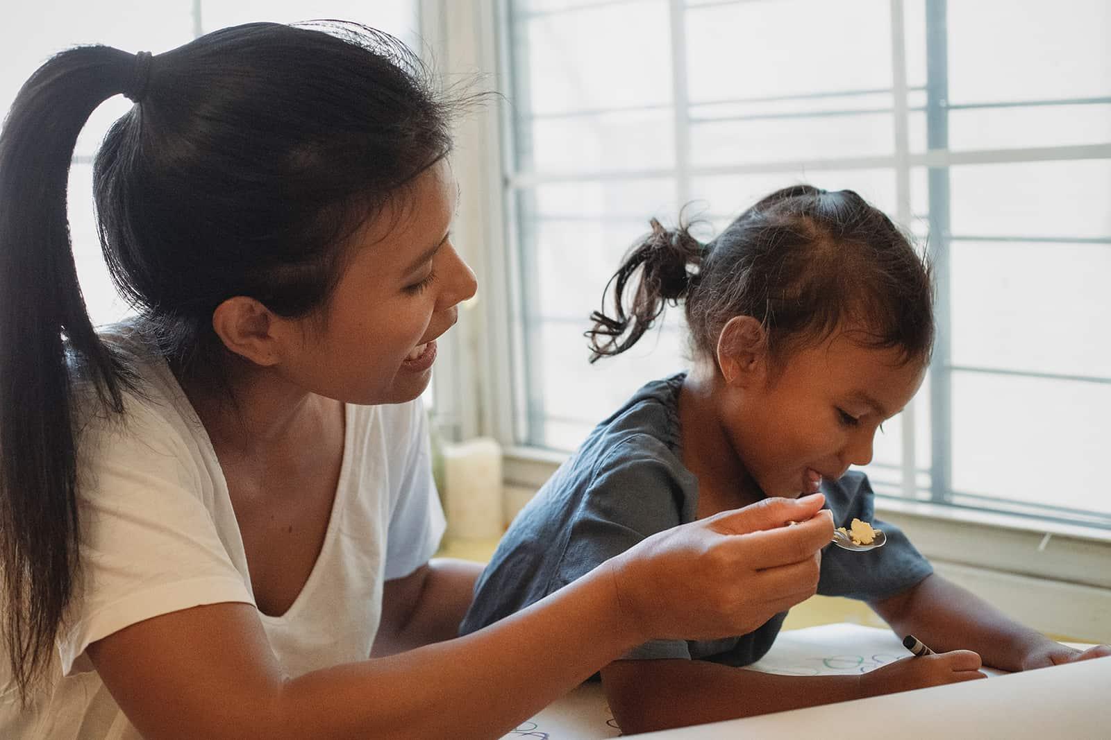 eine Mutter füttert ihr Kind zu Hause