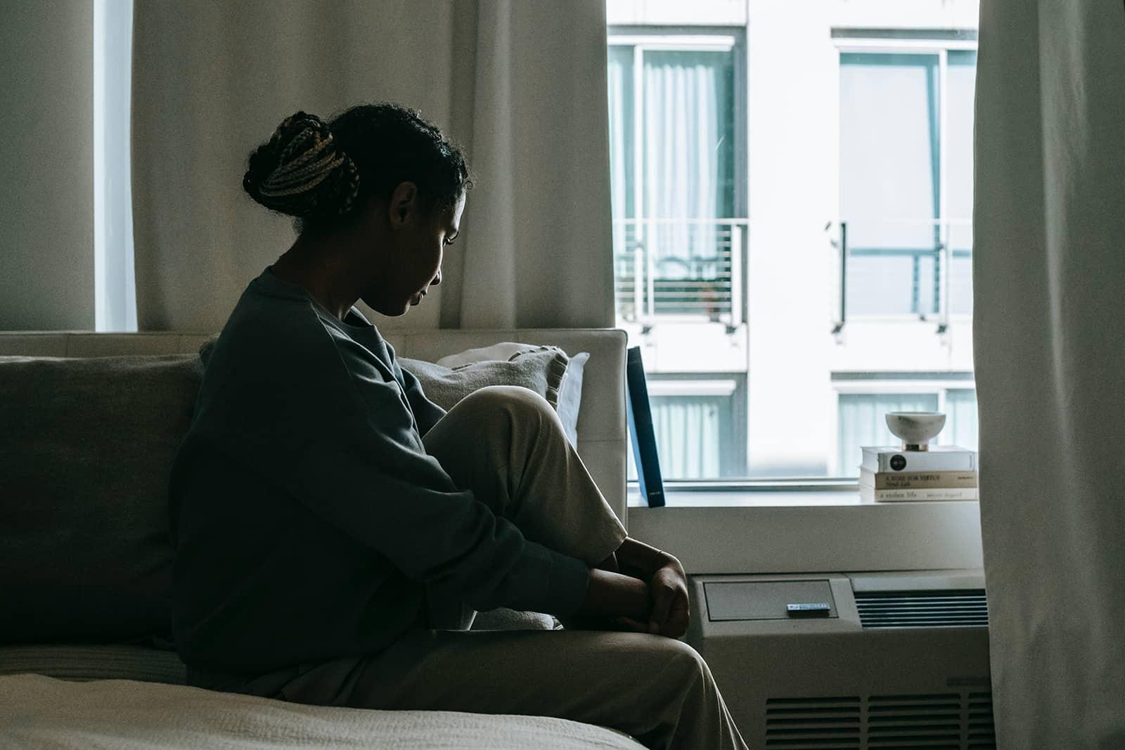 eine einsame Frau, die auf dem Bett sitzt und nach unten schaut