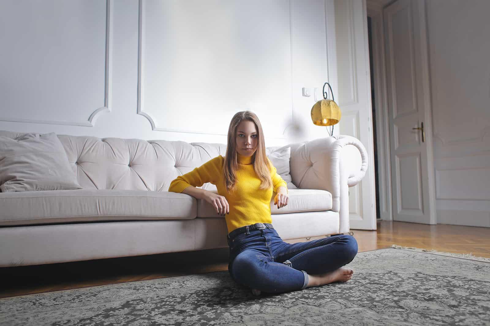eine junge Frau, die auf dem Boden sitzt und sich auf die Couch lehnt