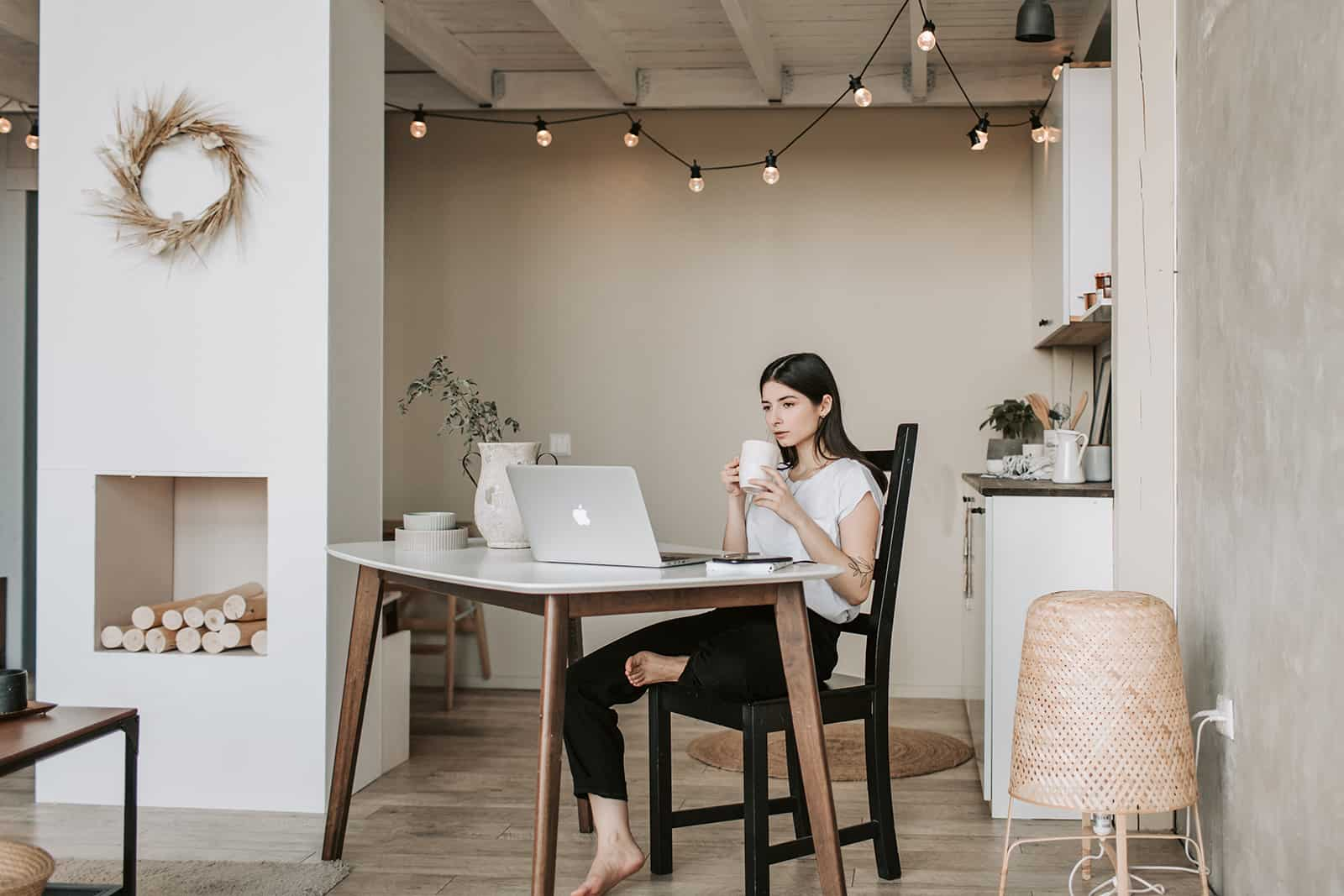 Eine konzentrierte Frau trinkt Kaffee, während sie zu Hause vor einem Laptop sitzt