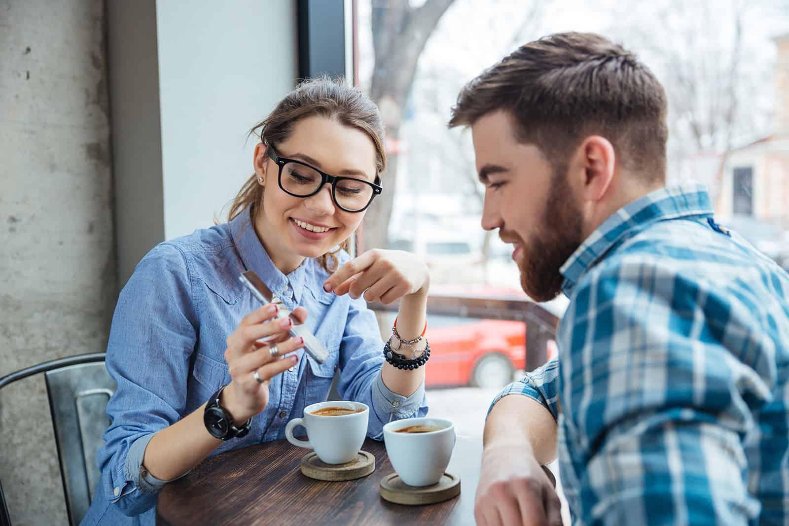 Eine lächelnde Frau zeigt einem Mann, der mit ihr im Café sitzt, ein Smartphone
