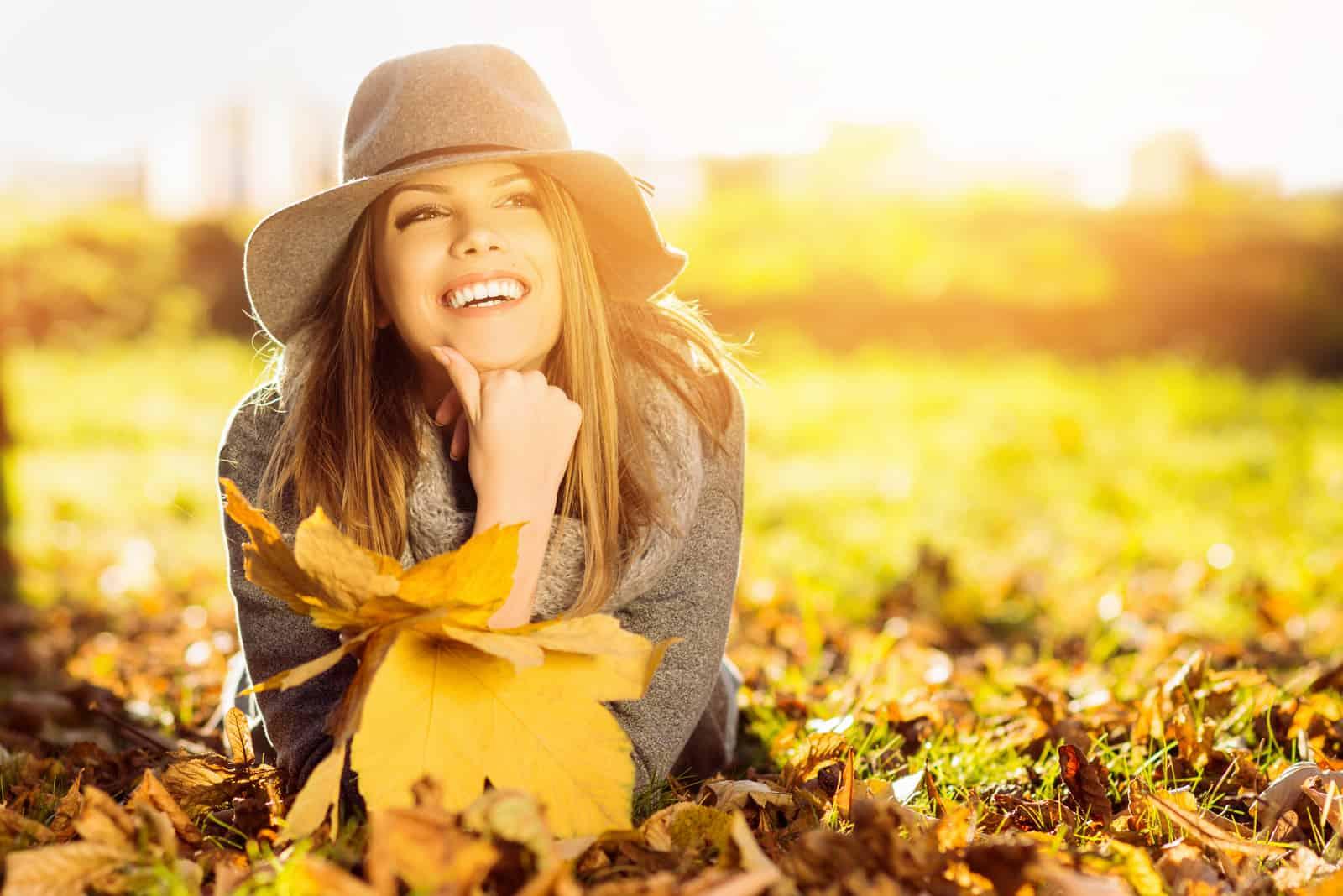 eine lächelnde Frau, die im Herbst auf einem Blatt liegt
