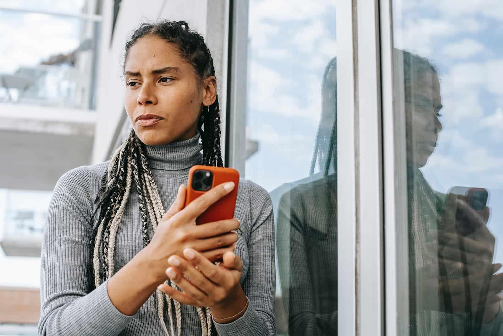 eine nachdenkliche Frau, die ihr Smartphone hält, während sie auf dem Balkon steht