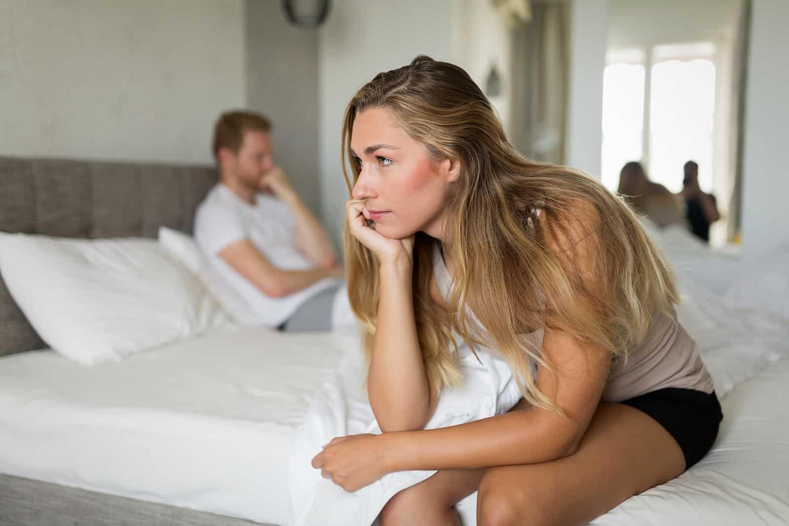 eine nachdenkliche Frau, die auf der Bettkante sitzt, während ein Mann hinter ihr liegt