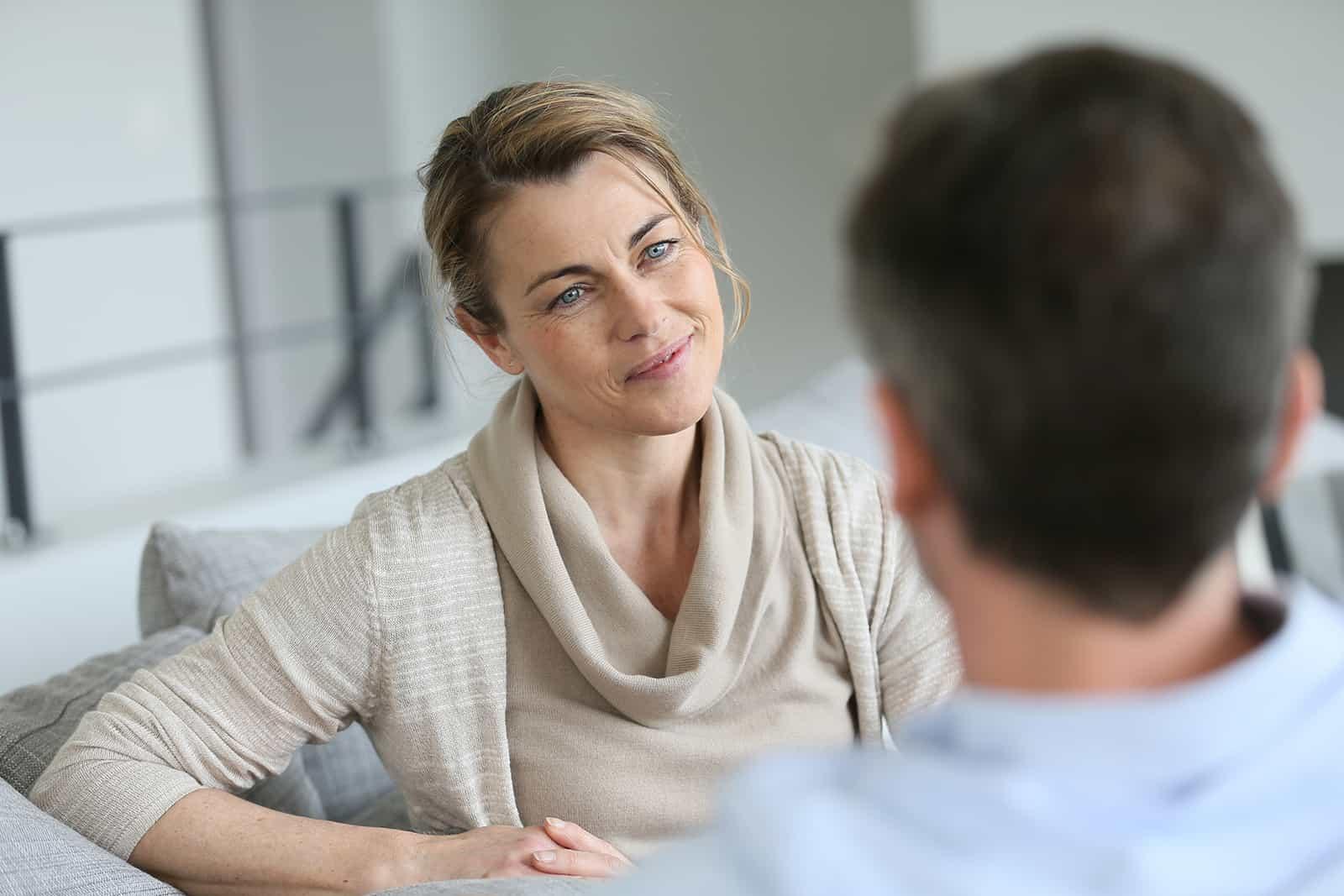 eine positive Frau, die einen Mann betrachtet, der mit ihr spricht, der auf der Couch sitzt