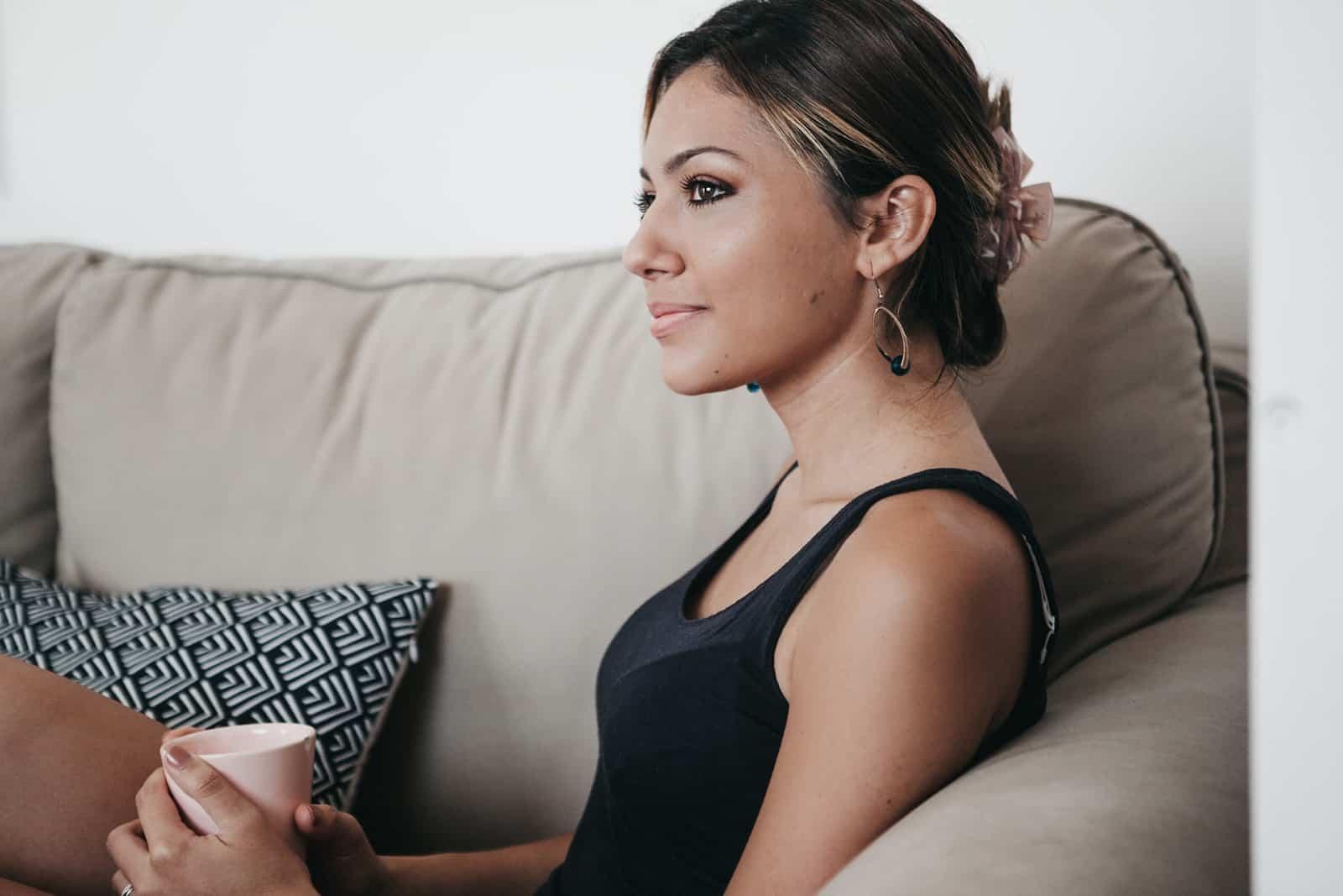 eine positive Frau, die auf der Couch sitzt und eine Tasse Kaffee hält