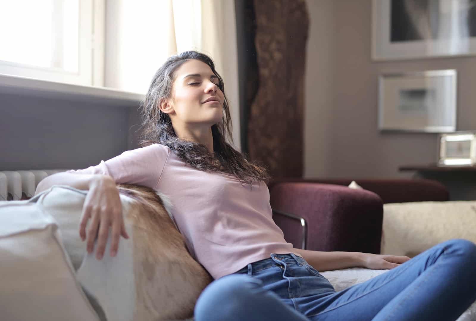 eine ruhige Frau, die mit geschlossenen Augen auf der Couch sitzt