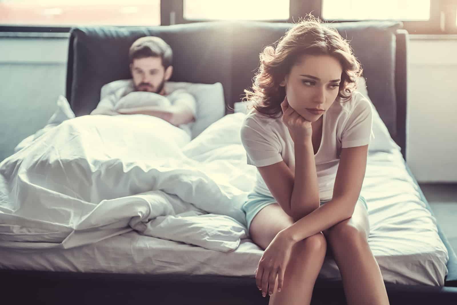 eine traurige Frau, die auf der Bettkante sitzt, während ein Mann hinter ihr liegt