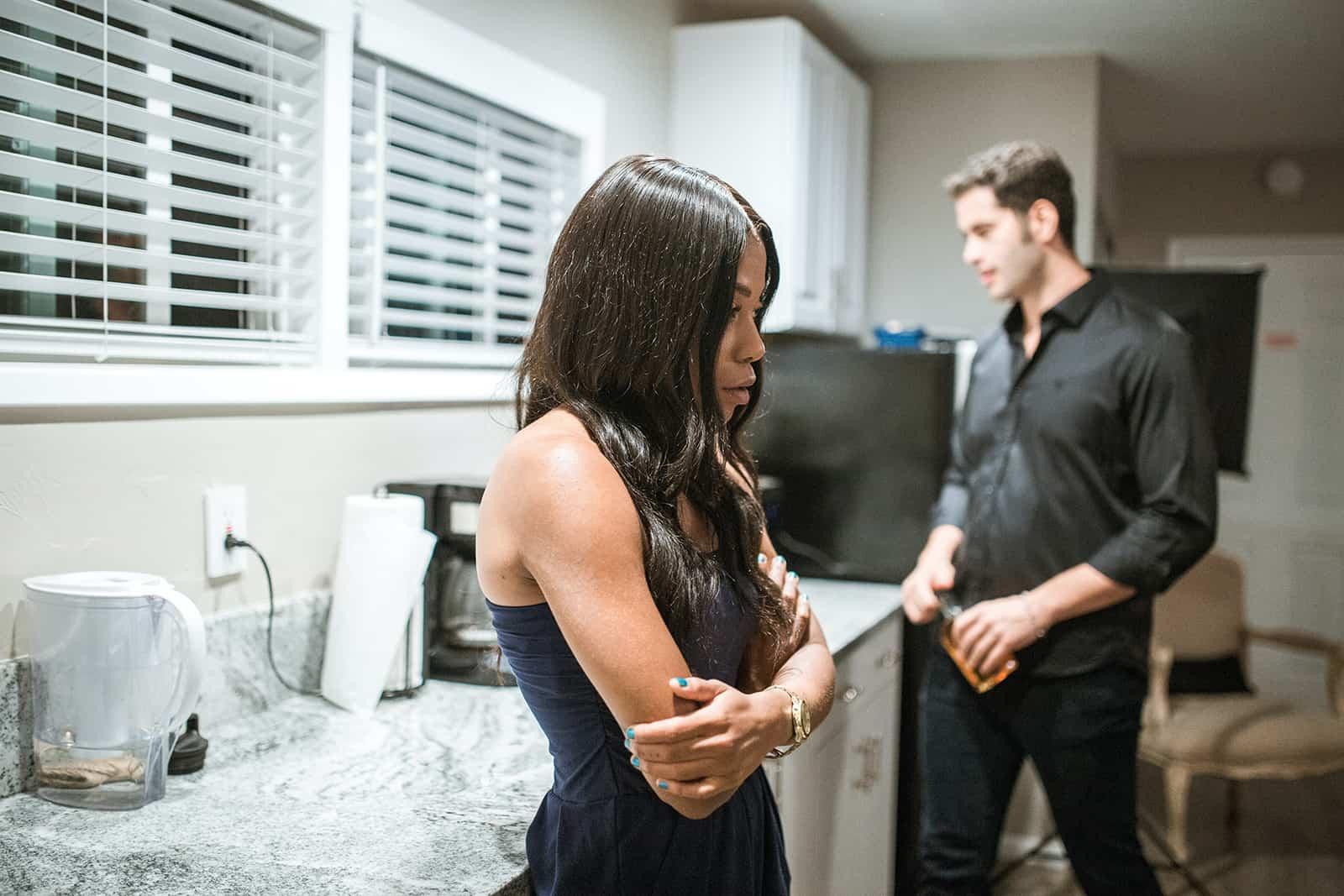 eine traurige Frau, die in der Küche steht, während ihr Mann eine Flasche Getränk hält