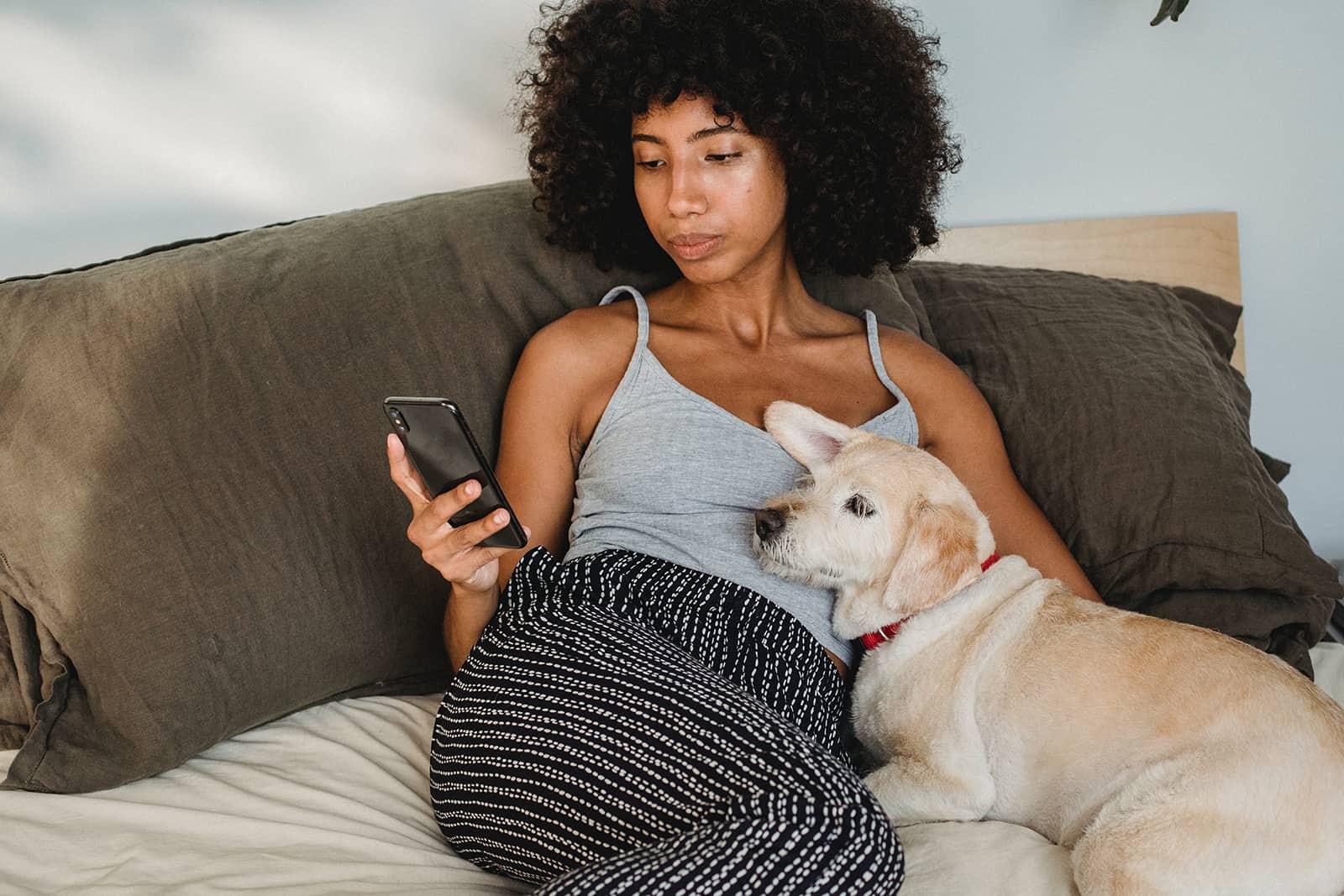eine verärgerte Frau, die ein Smartphone betrachtet, das mit Hund auf dem Bett liegt