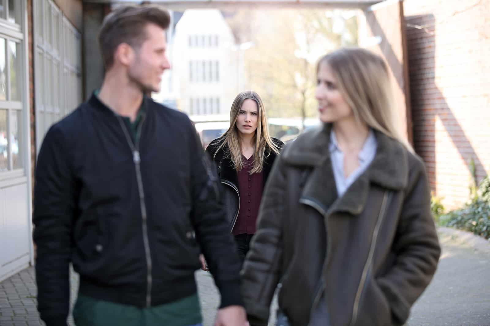 eine verwirrte Frau, die ein liebendes Paar vor sich betrachtet, während sie auf dem Bürgersteig geht