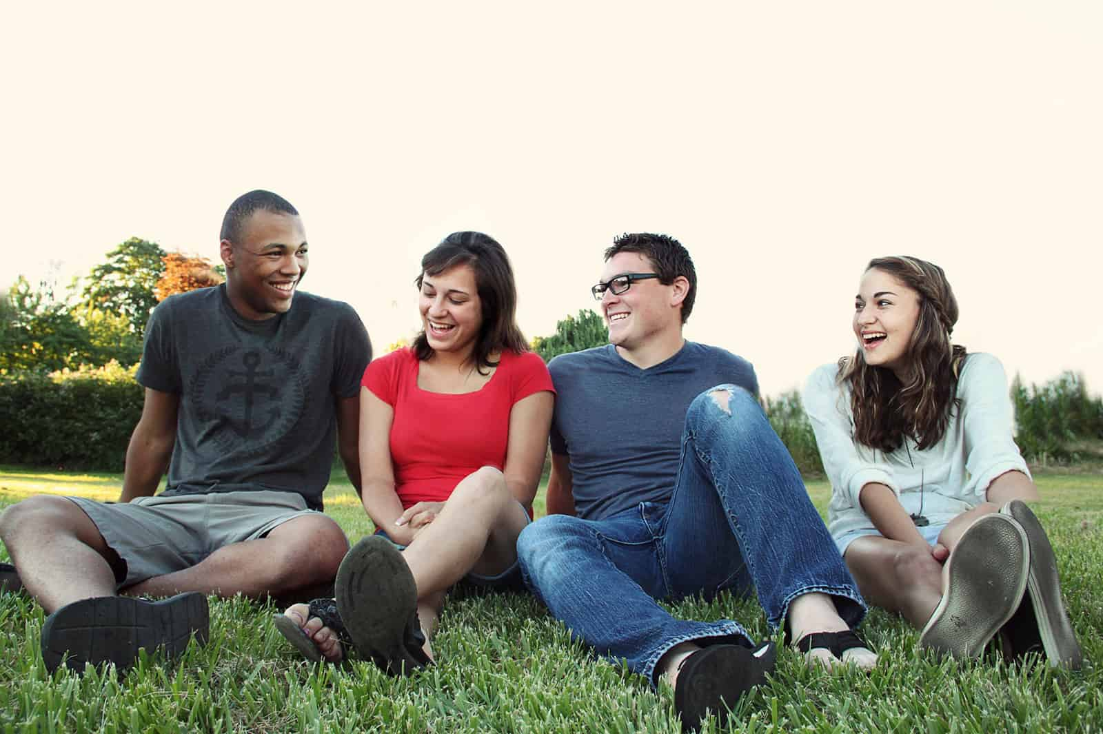 fröhliche Freunde sitzen auf dem Rasen beim Abhängen