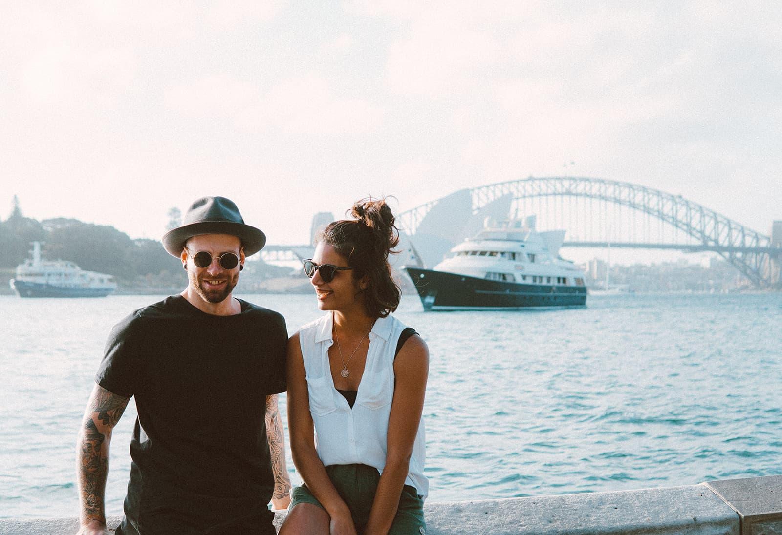 fröhlicher Mann und Frau sitzen auf der Betonmauer nahe dem Fluss