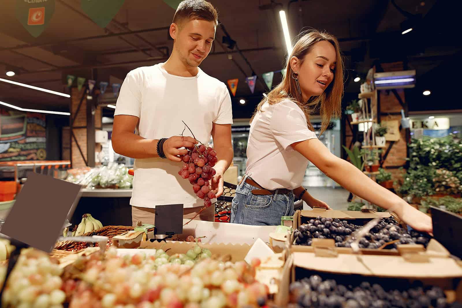 fröhliches Paar, das Früchte auf dem Markt wählt