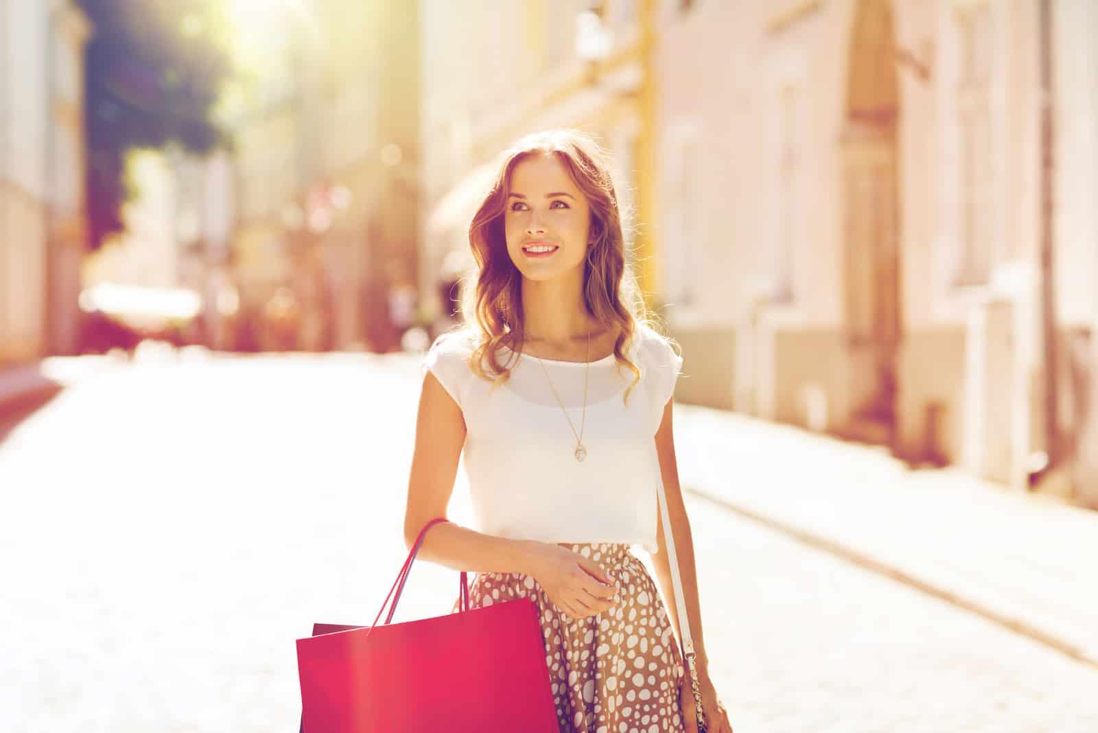 glückliche junge Frau mit Einkaufstüten, die entlang Stadtstraße gehen