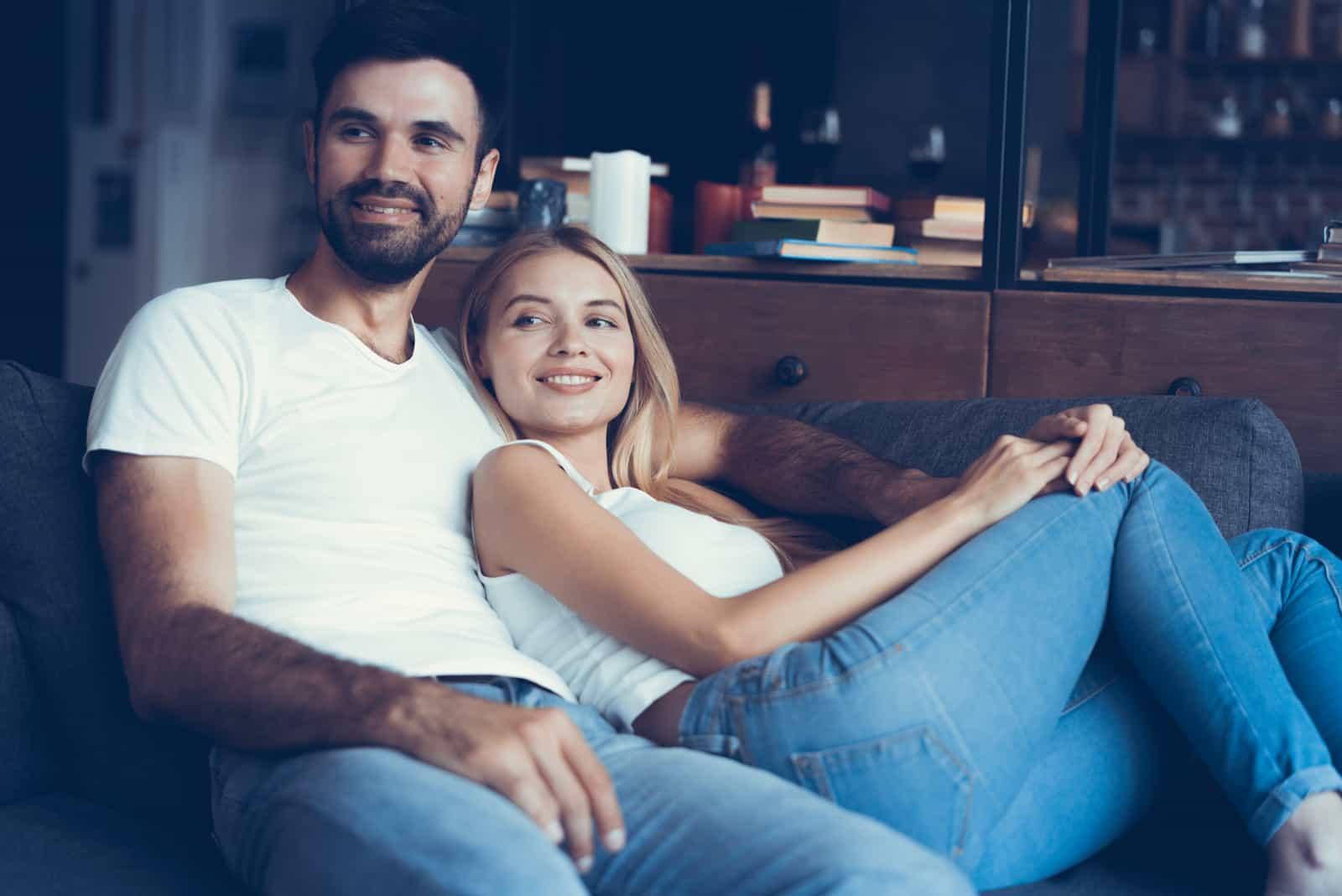 glückliches Paar, das auf der Couch sitzt und fernsieht