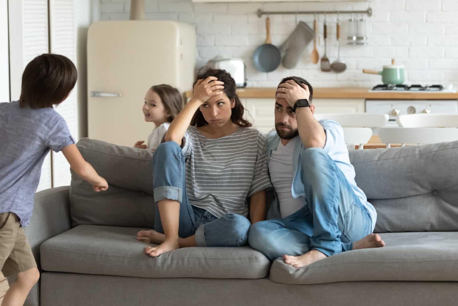 junge Eltern sitzen unter Stress auf der Couch und beobachten die schelmischen Kinder