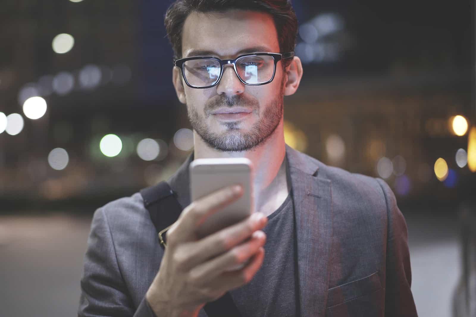 lächelnder Mann, der Smartphone betrachtet, während er nachts draußen steht