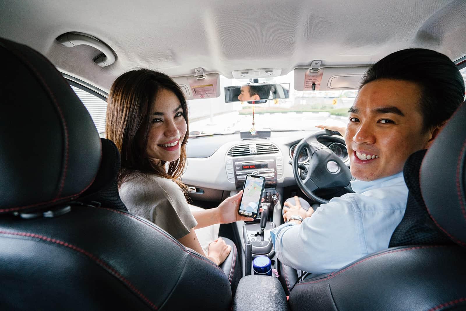 lächelnder Mann und eine Frau sitzen im Auto und schauen nach hinten