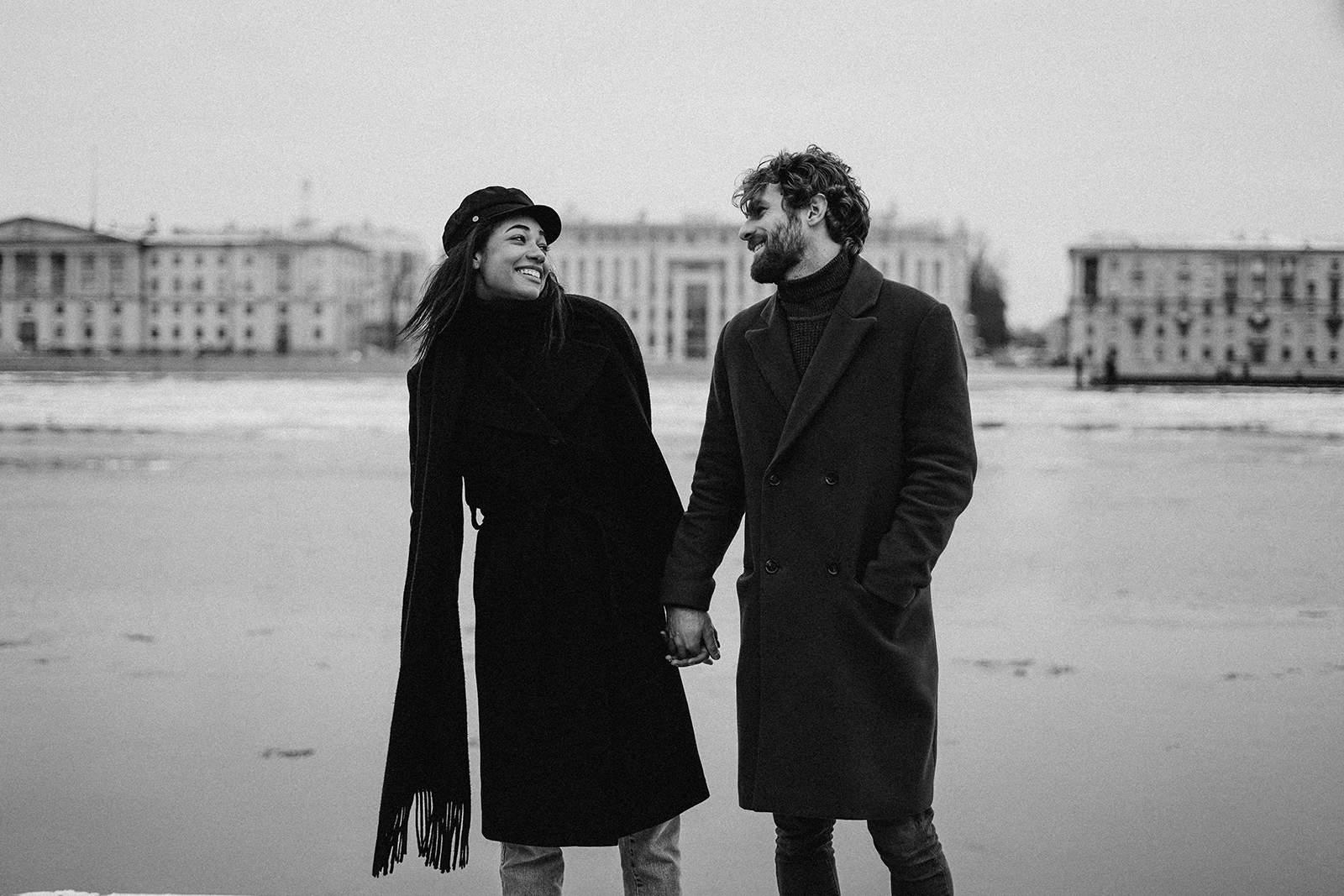lächelndes Paar Händchen haltend und einander ansehend