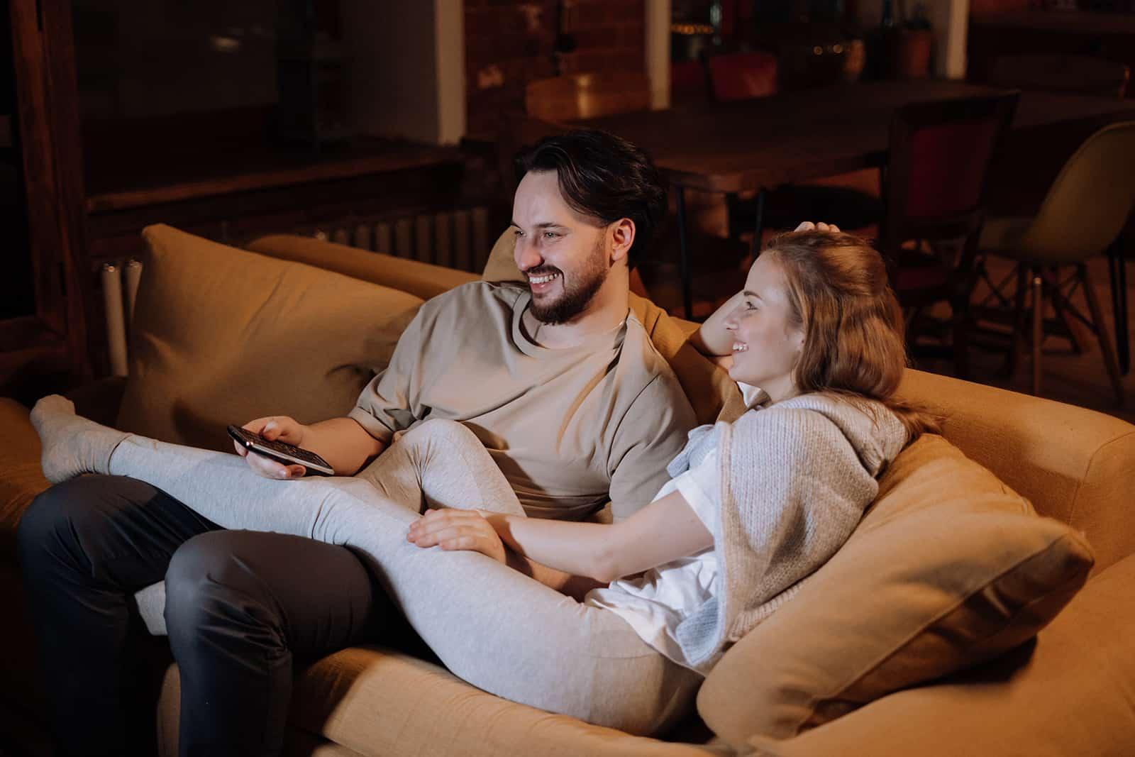 lächelndes Paar, das abends auf der Couch kuschelt