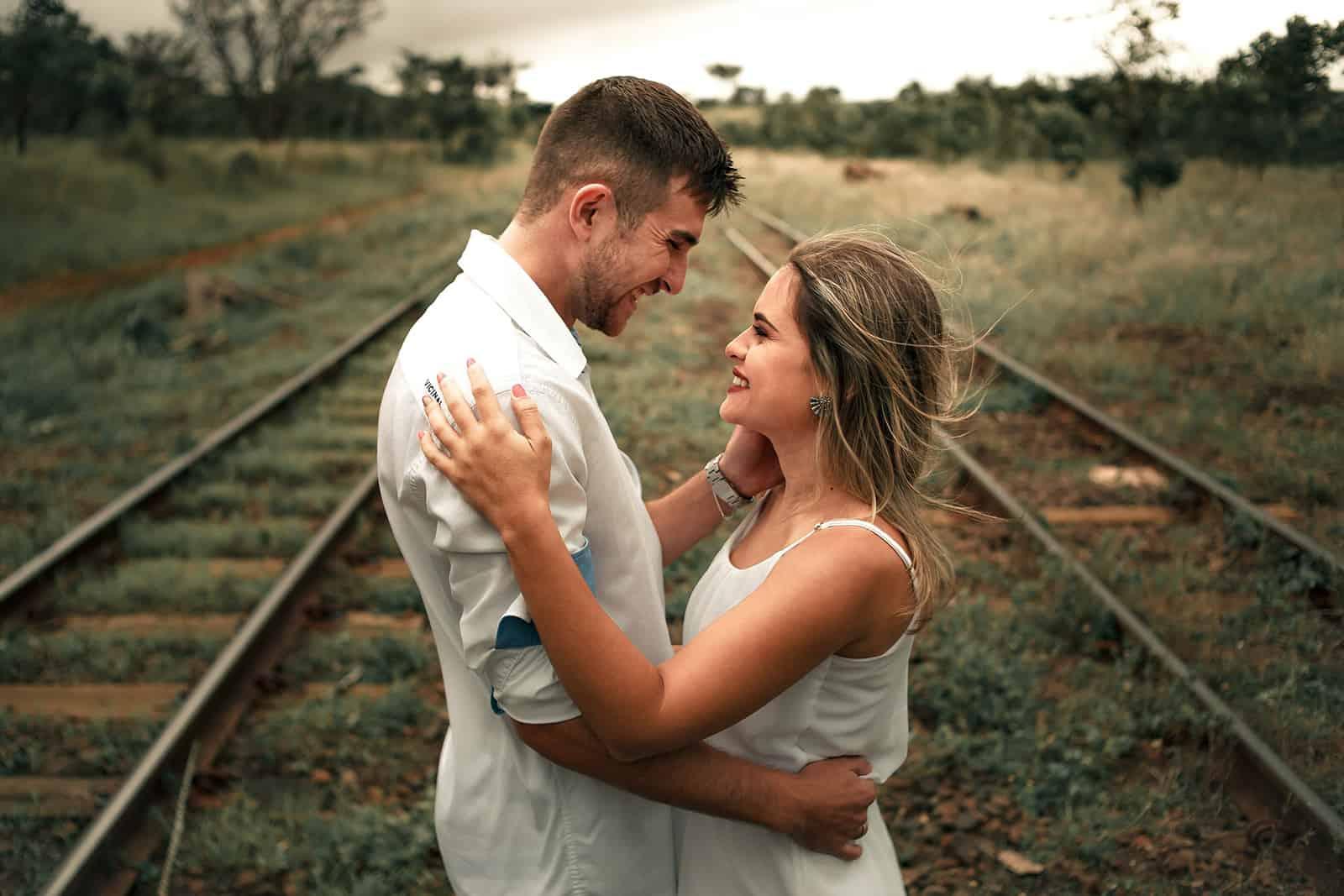 lächelndes Paar umarmt und einander gegenüber stehend auf der Schiene