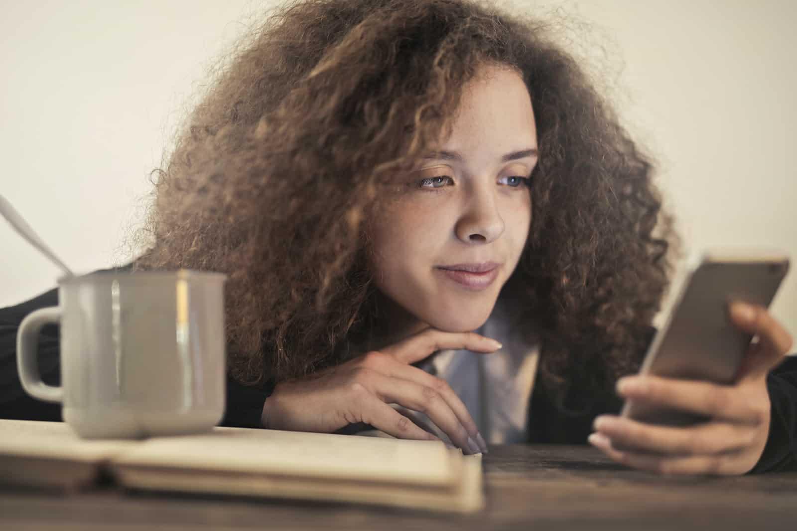 nachdenkliche Frau, die Smartphone beim Anlehnen auf dem Tisch betrachtet
