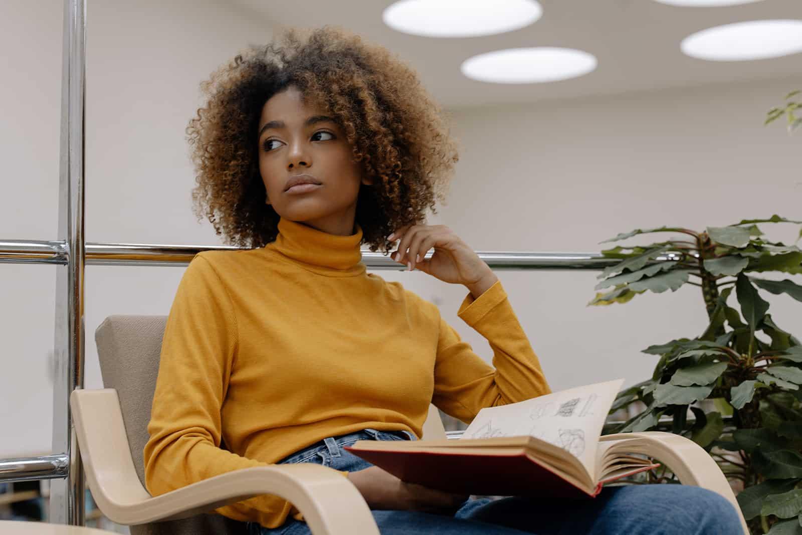 nachdenkliche Frau, die beiseite schaut, während sie ein Buch hält