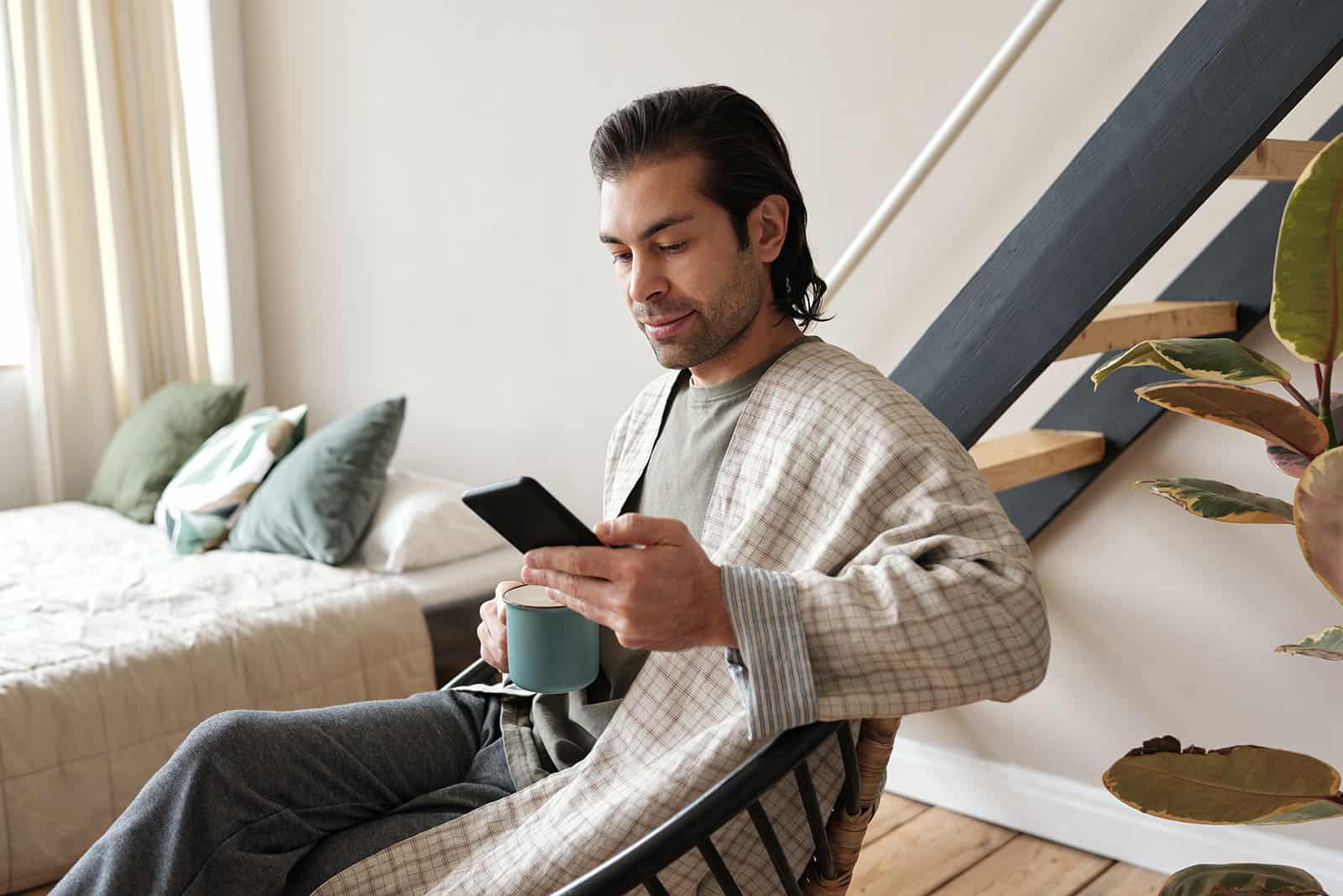 nachdenklicher Mann, der Smartphone beim Sitzen im Sessel zu Hause betrachtet