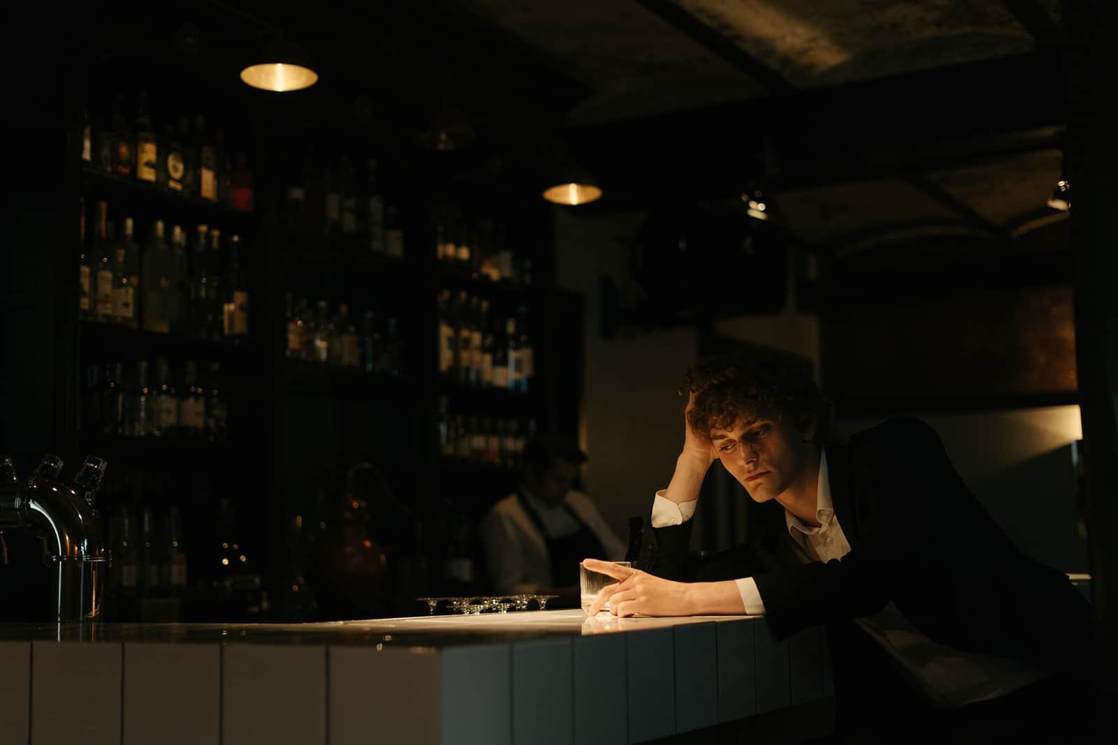 nachdenklicher Mann, der alleine an der Theke sitzt und auf sein Date wartet
