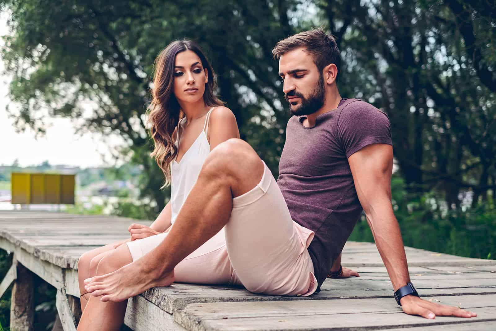 nachdenklicher Mann sitzt neben seiner Freundin auf dem Dock