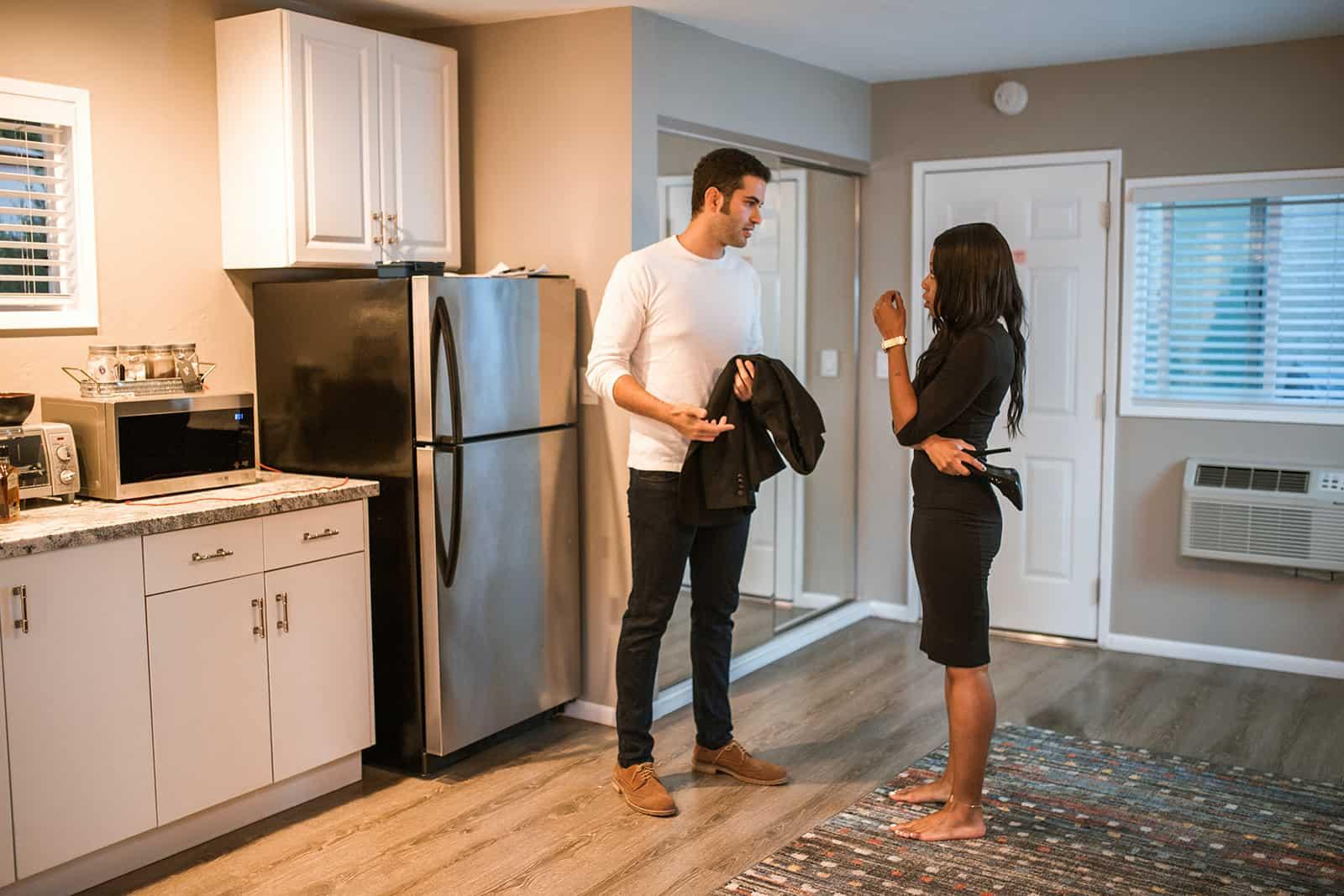 verärgerte Frau im Gespräch mit einem Mann, der in ihre Wohnung kam