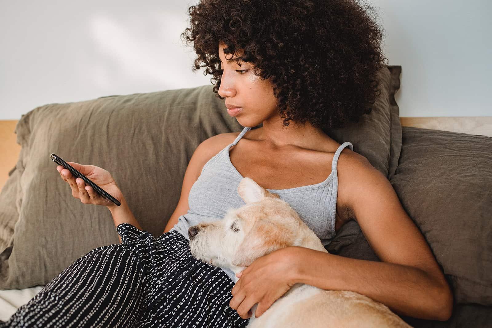 verwirrte Frau, die Smartphone betrachtet und mit einem Hund auf der Couch sitzt