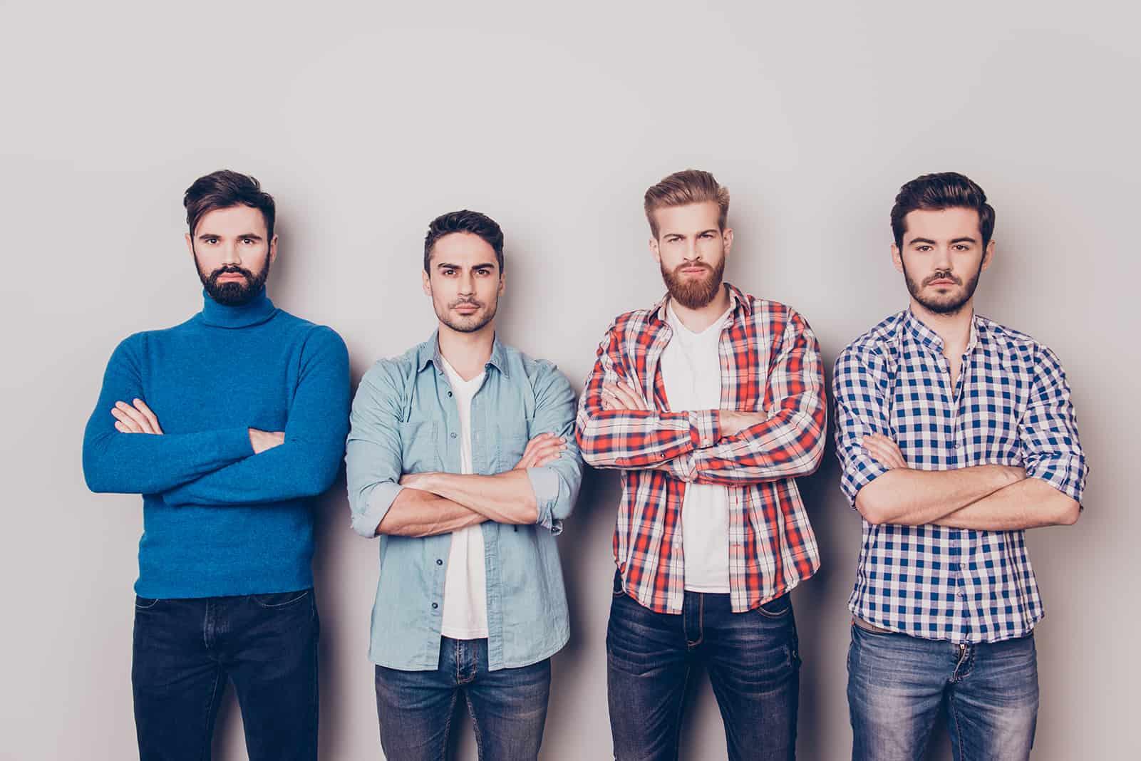 vier Männer nebeneinander, alle mit verschränkten Armen