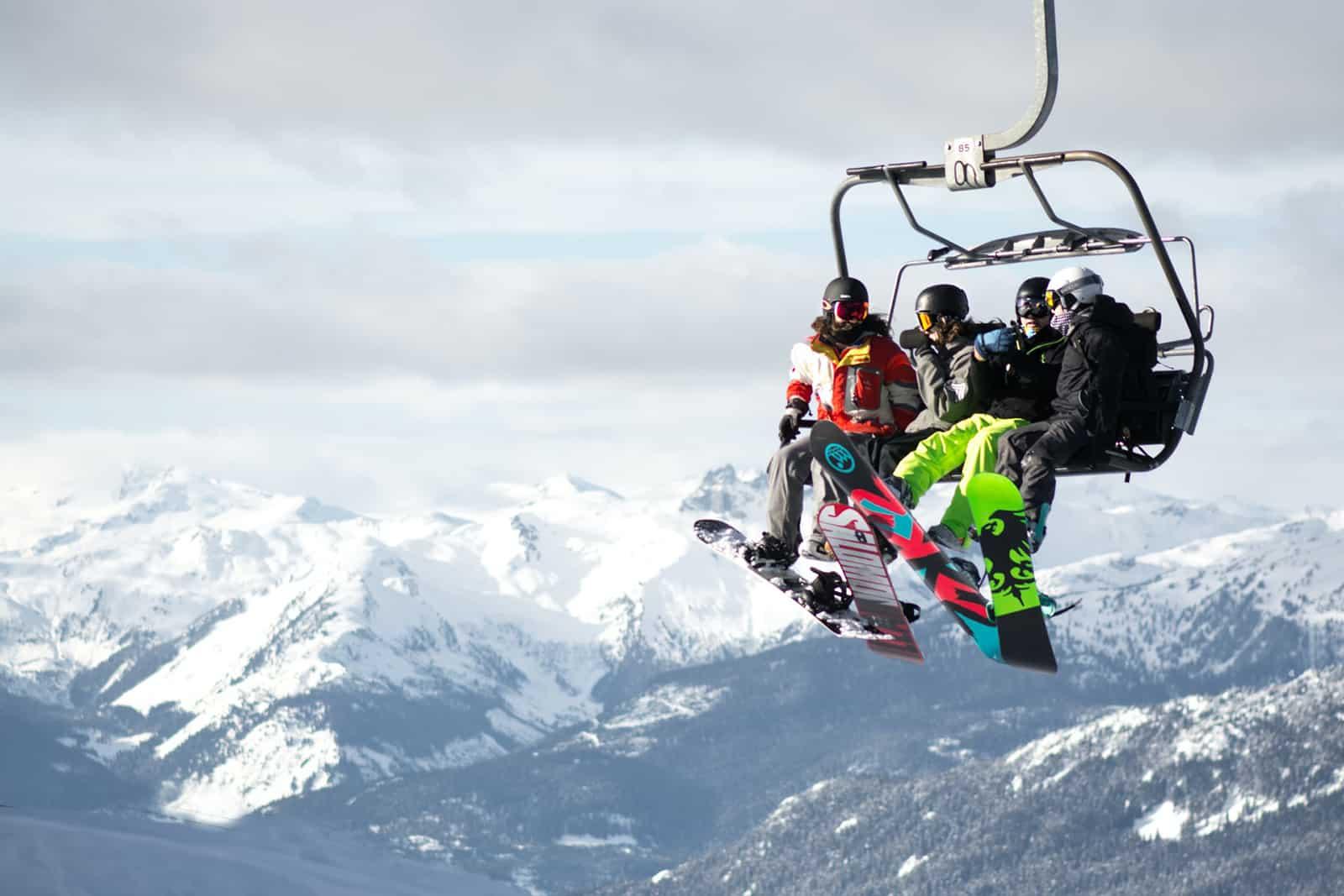 vier Personen fahren mit einer Seilbahn in den Bergen
