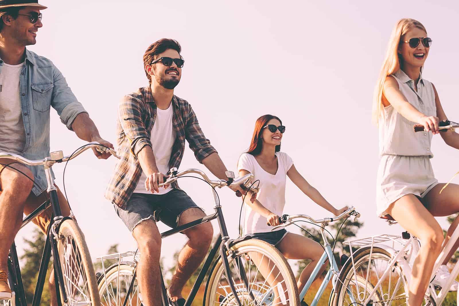 vier fröhliche Freunde, die an einem sonnigen Tag Fahrrad fahren