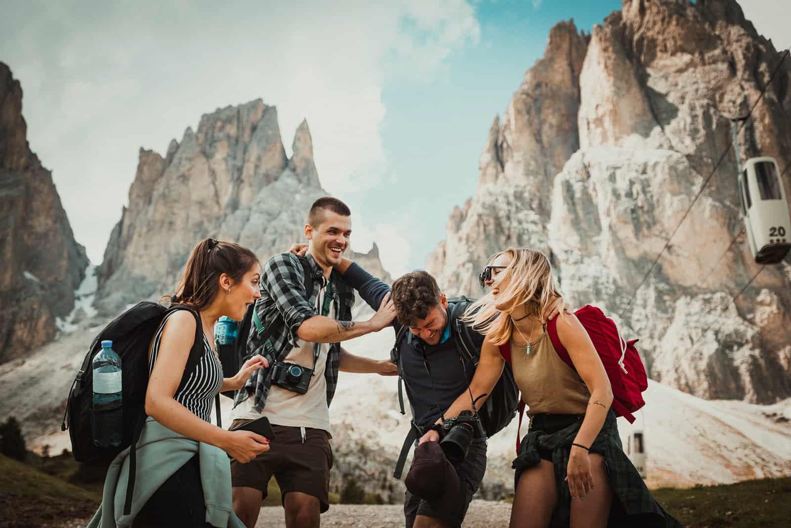 vier lachende Freunde, die beim Wandern im Berg stehen