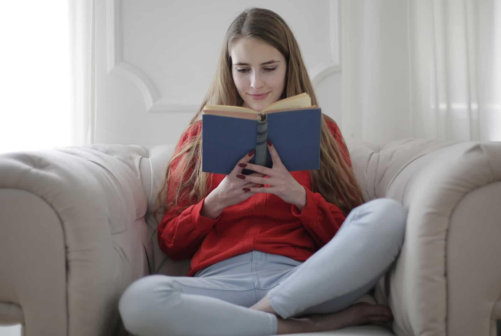 zufriedene Frau, die Buch liest, das auf einem Sessel sitzt