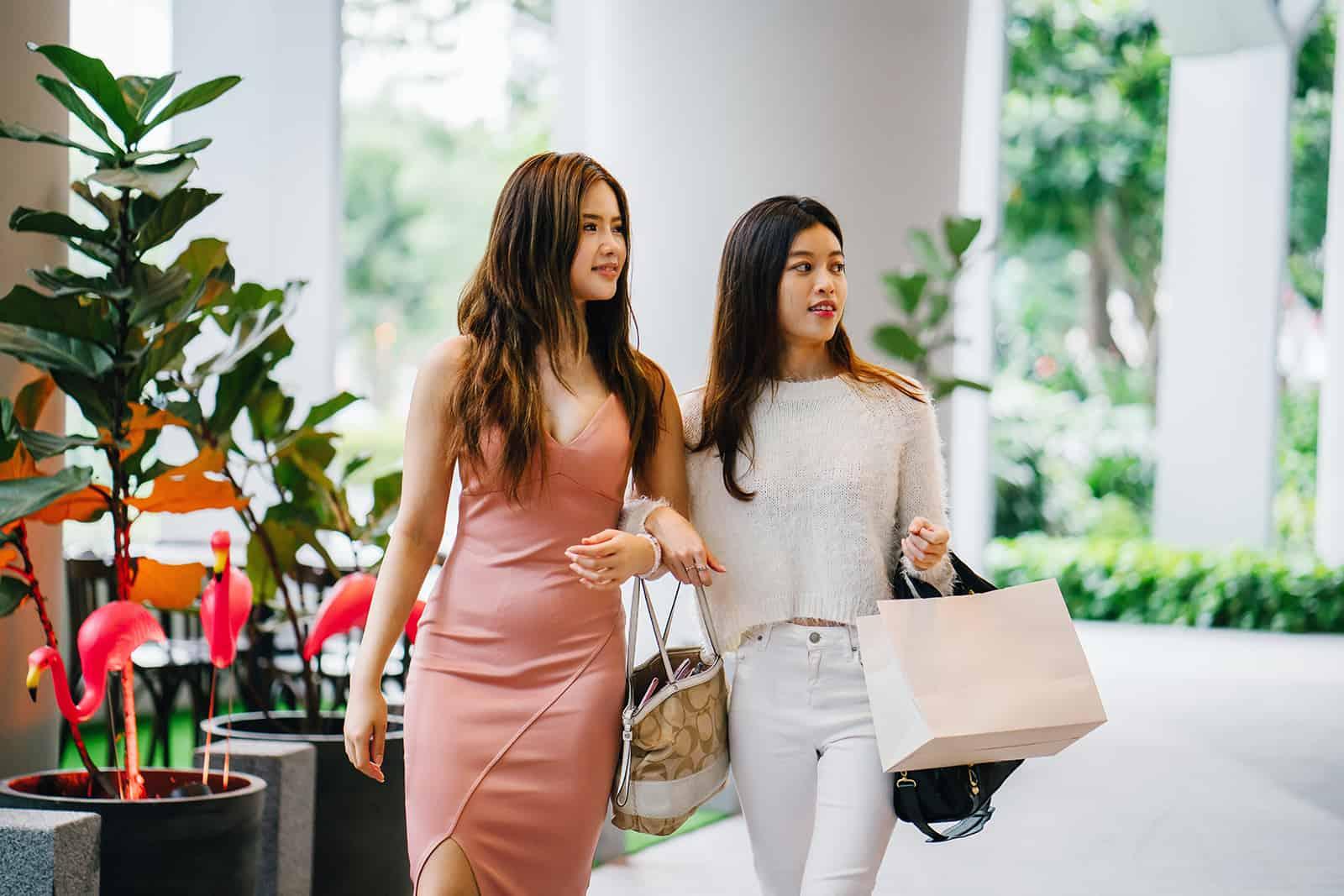 zwei Freundinnen, die beim gemeinsamen Einkaufen nebeneinander gehen