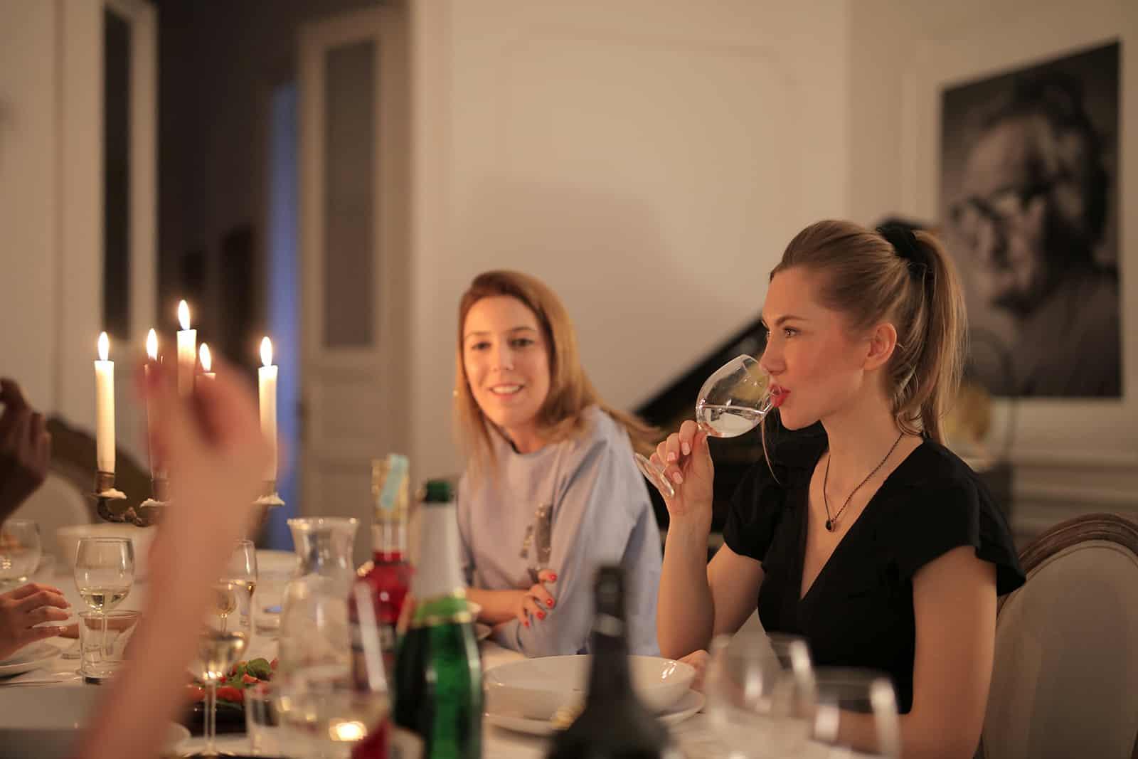 zwei Freundinnen sitzen am Tisch und haben Spaß beim Abendessen