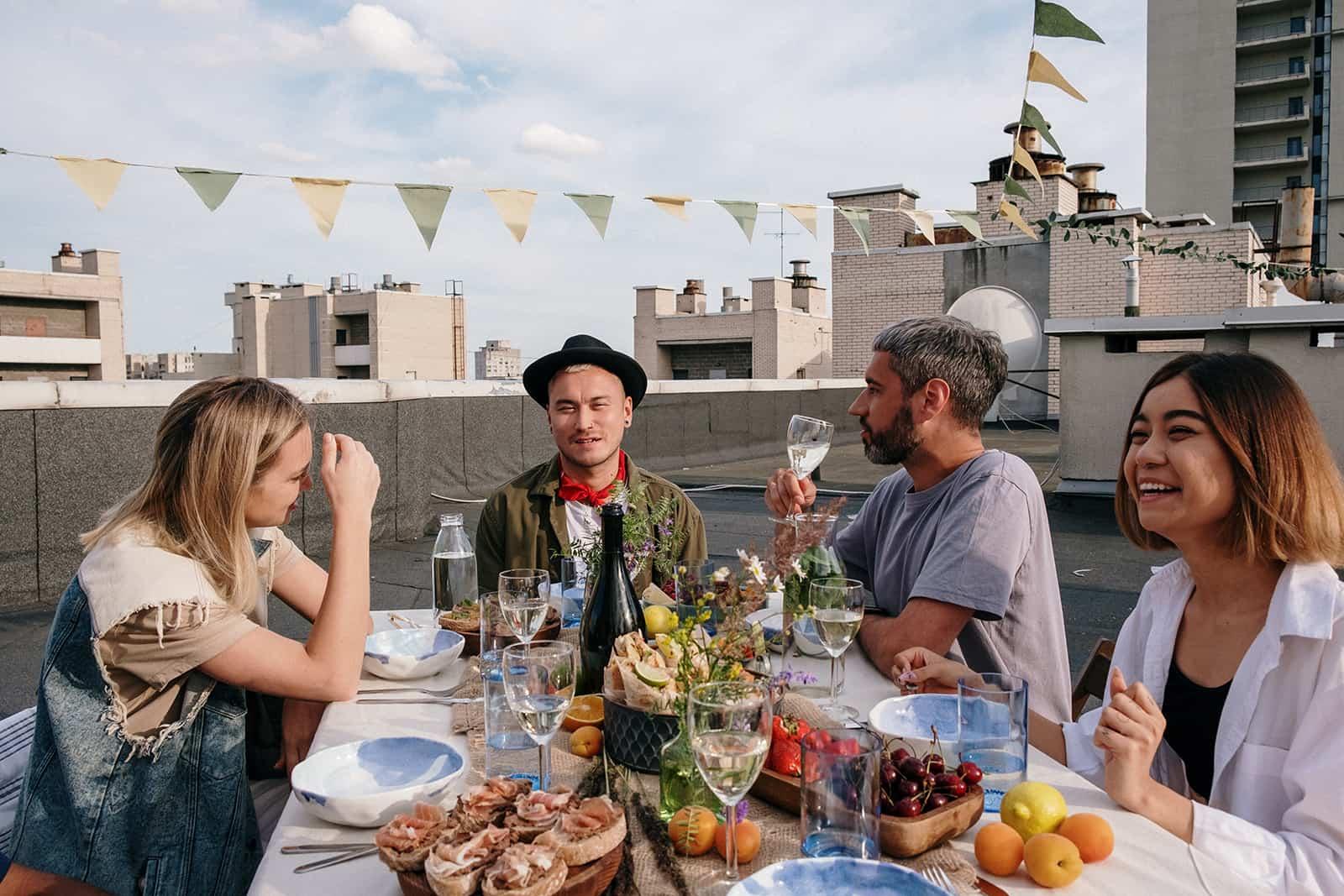 Zwei Paare unterhalten sich während eines Essens auf dem Dach bei einem Doppeldate