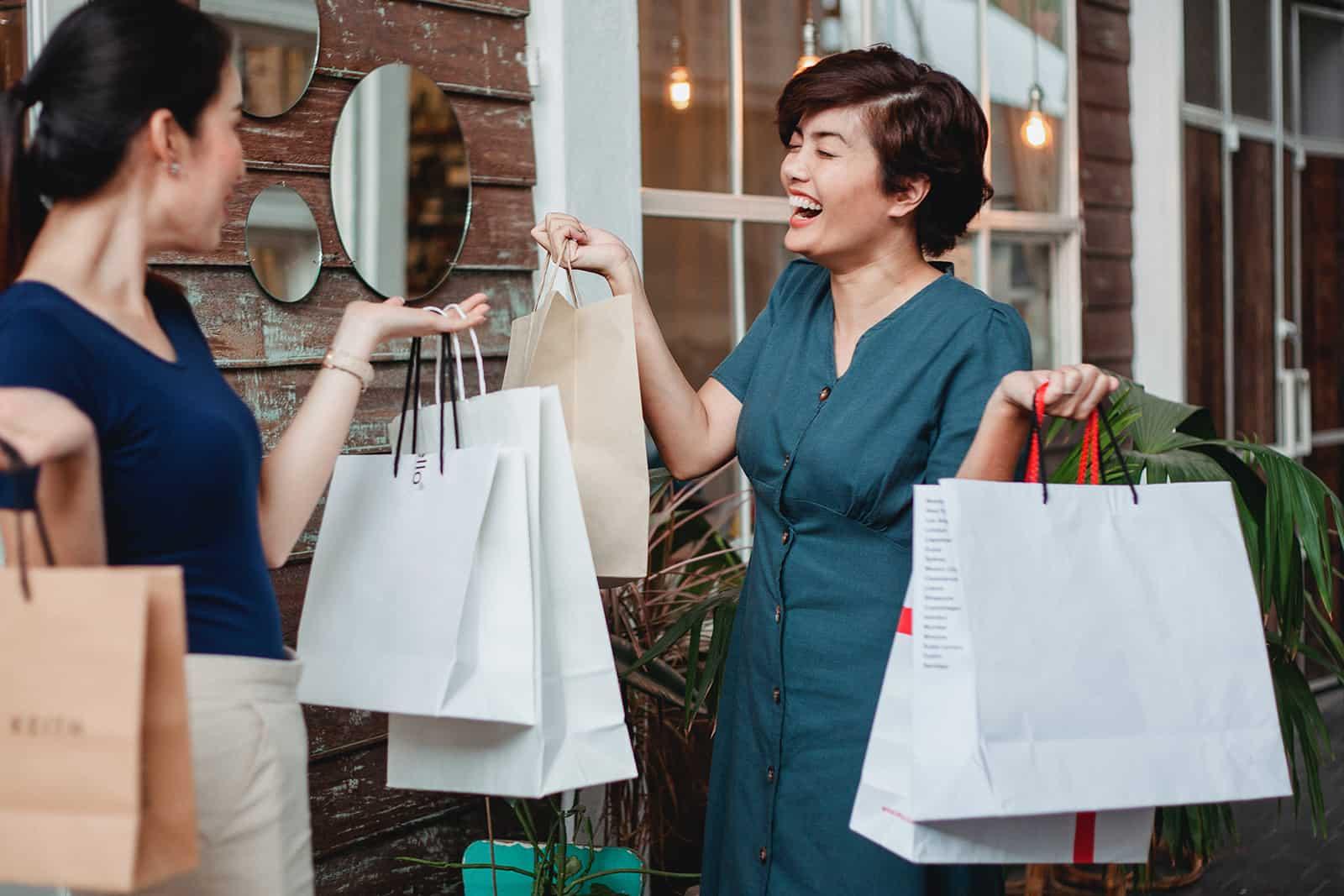zwei glückliche Freundinnen, die Einkaufstaschen halten, während sie vor dem Haus stehen